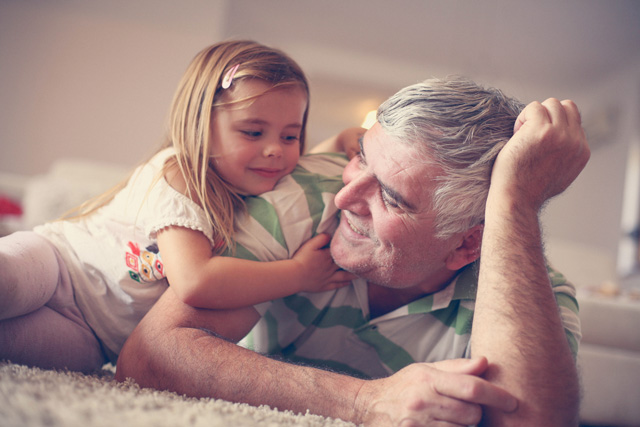 A picture of a grandfather and granddaughter playing together. Represents the connection between grantors, trustees and beneficiaries.