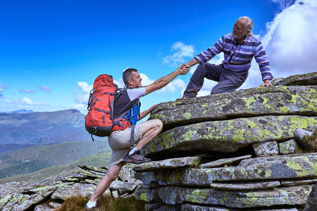 A hiker helping another hiker up onto a large rock. Represents the help that Whalen Financial Planning provides to trust beneficiaries.