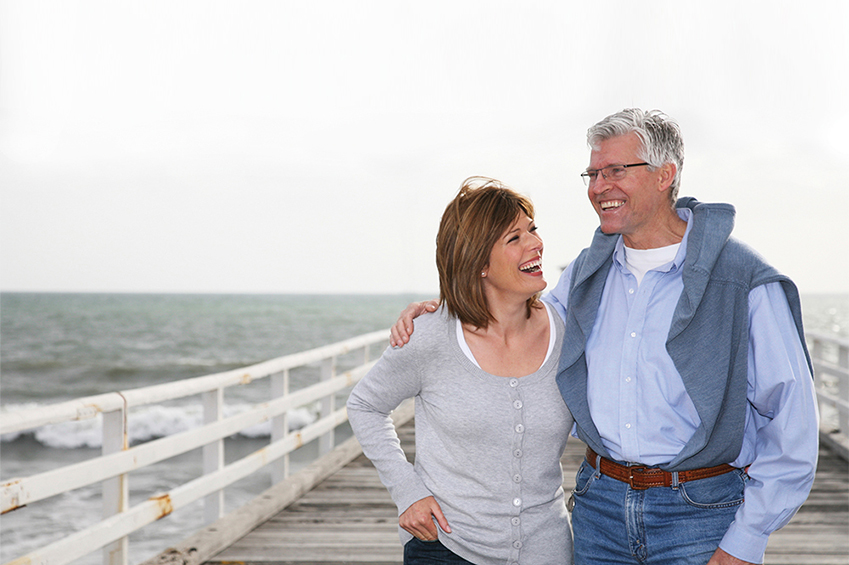 Older couple walking on pier.