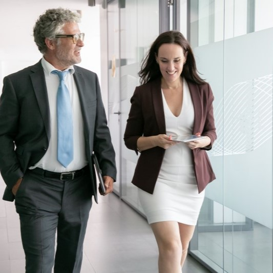 Businessman and businesswoman walking down office hallway