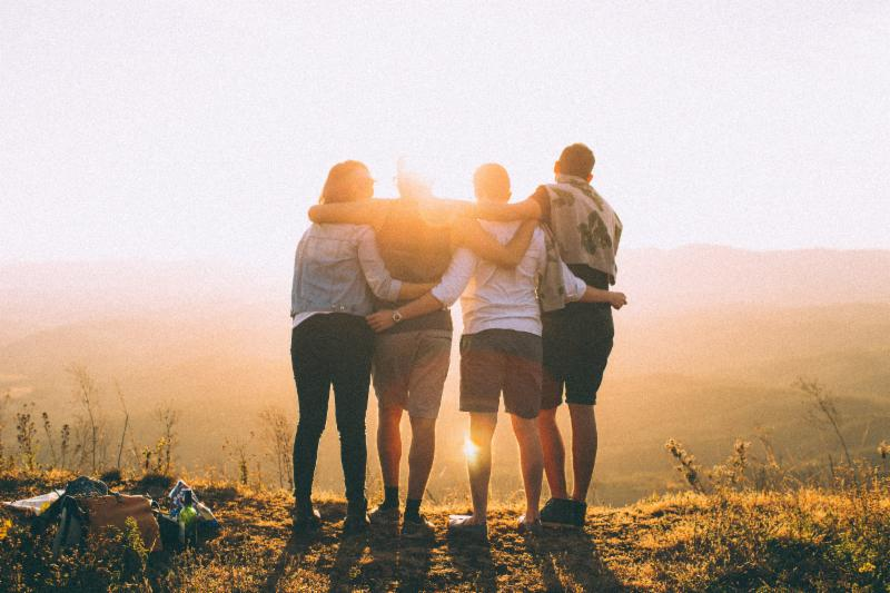 Family embracing while watching the sun set.