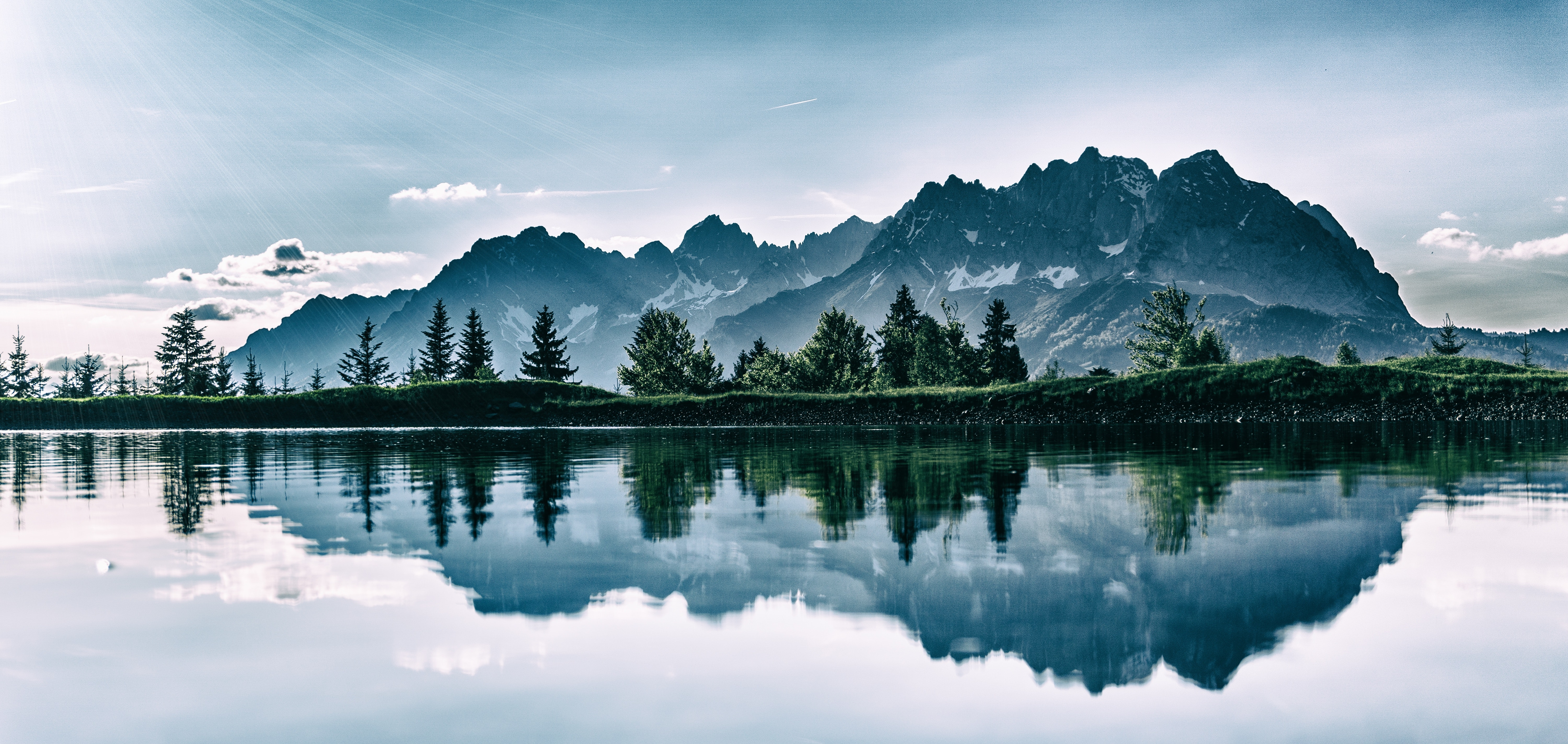 photo of a still lake under snowy mountains