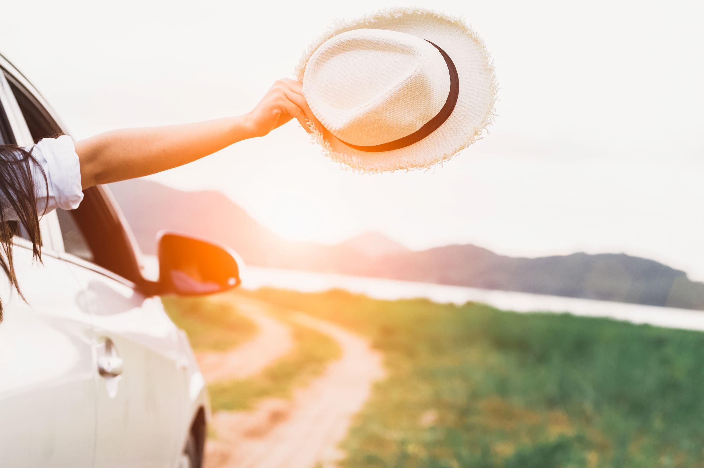 Une femme met son chapeau hors de la fenetre d'automobile.