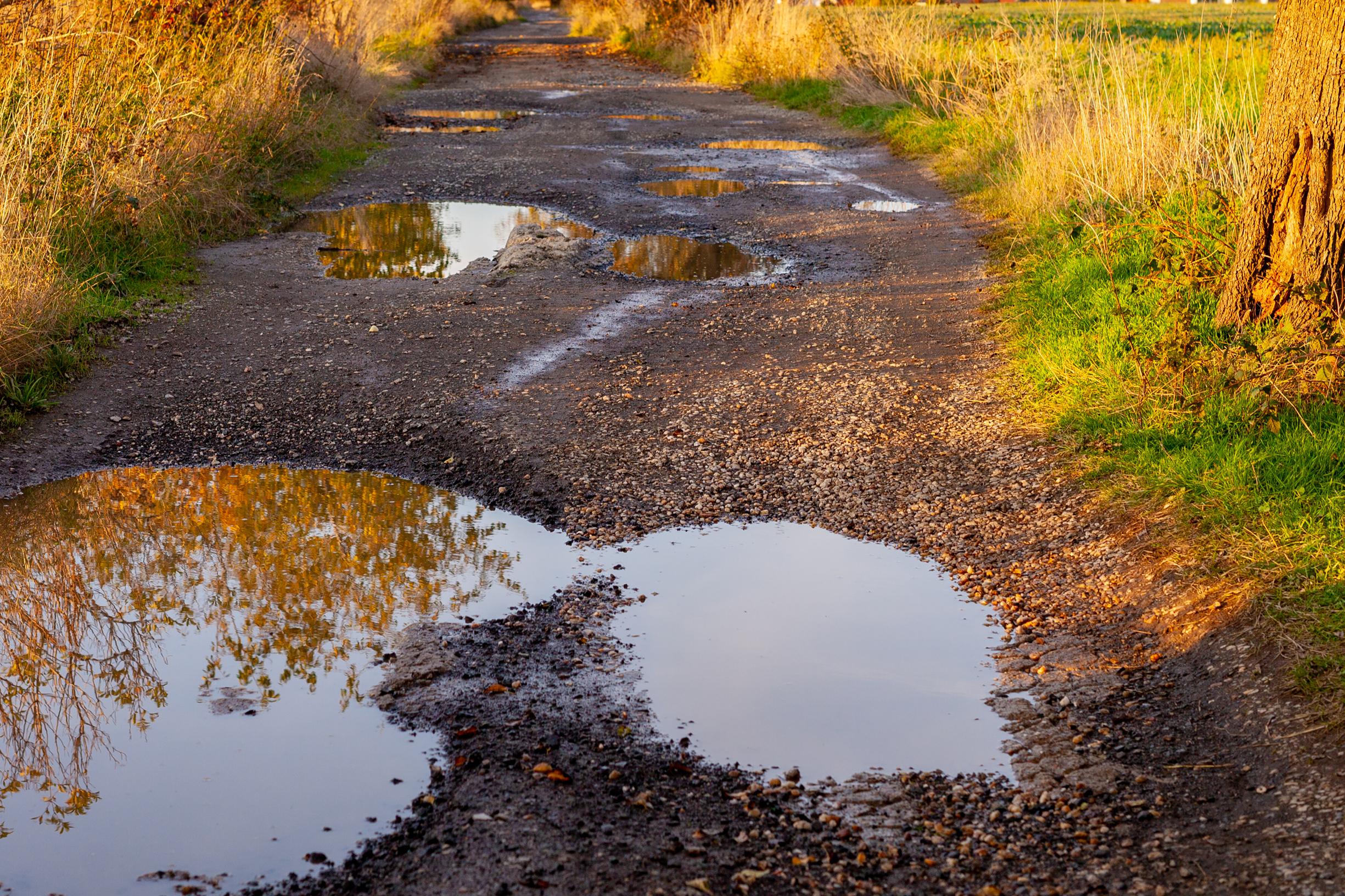 image of road full of potholes