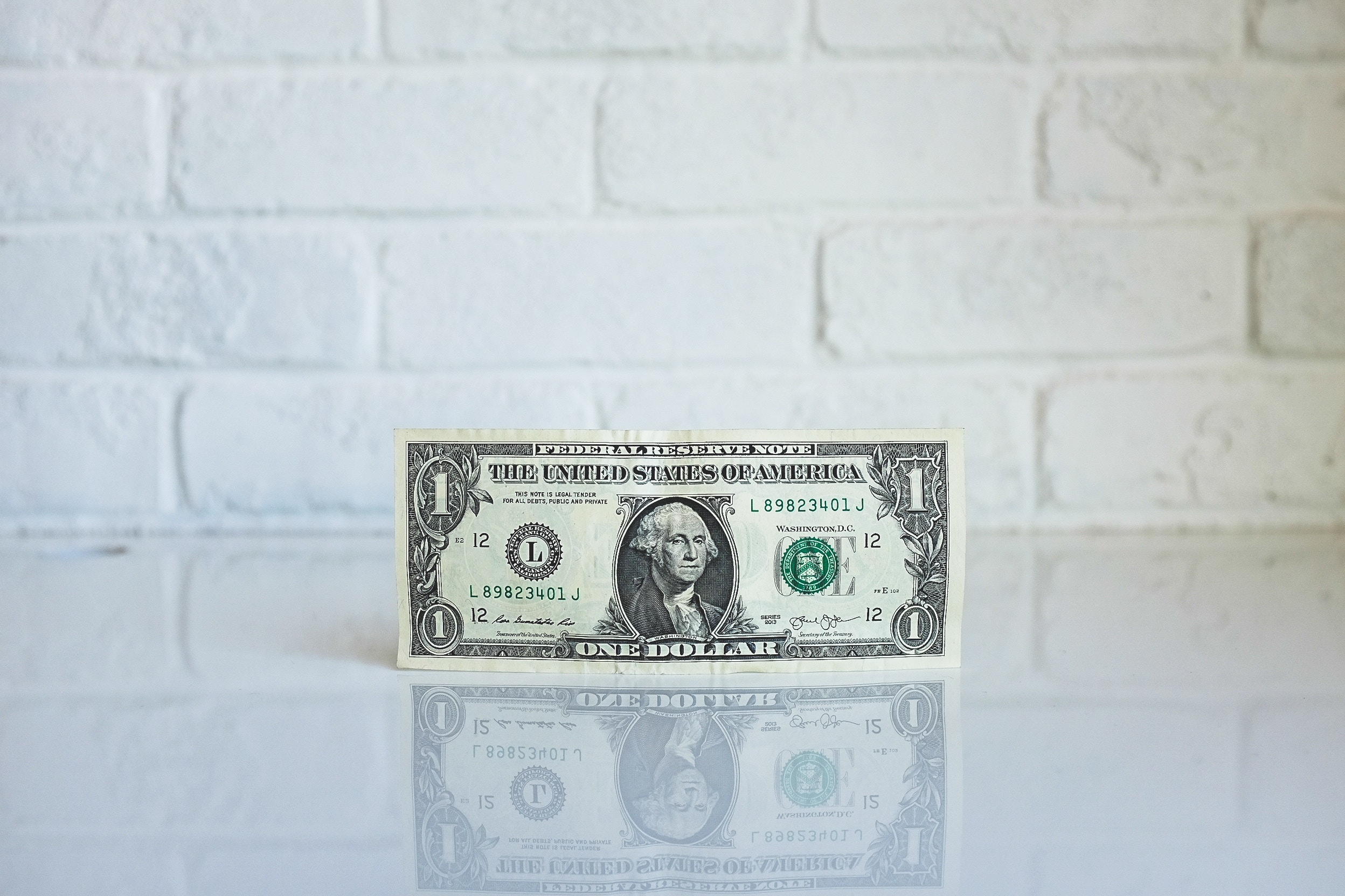 Front of a US dollar bill in front of white brick wall