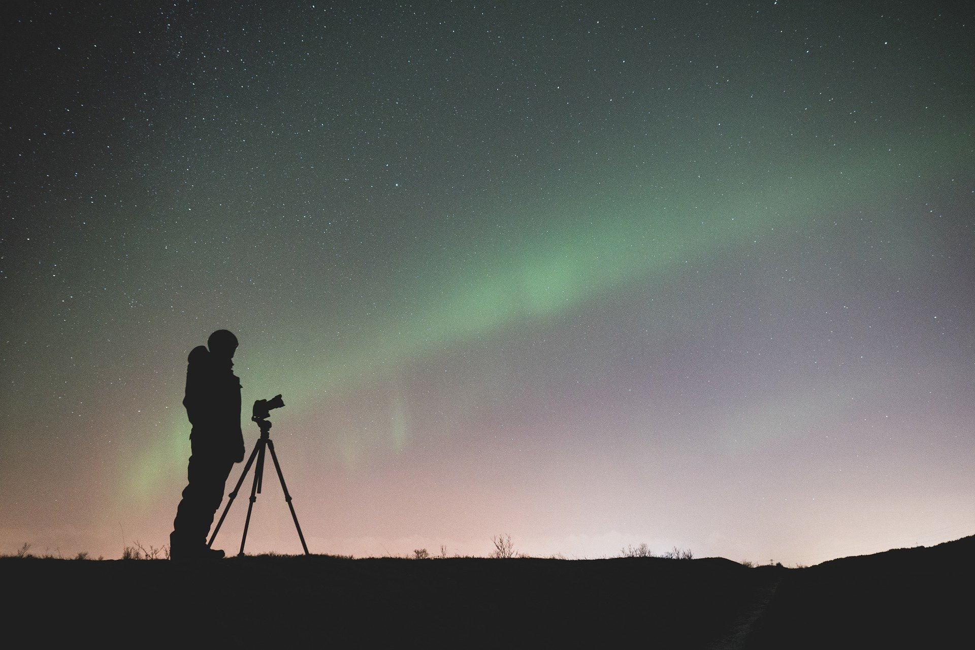 silhouette of a photographer against northern lights