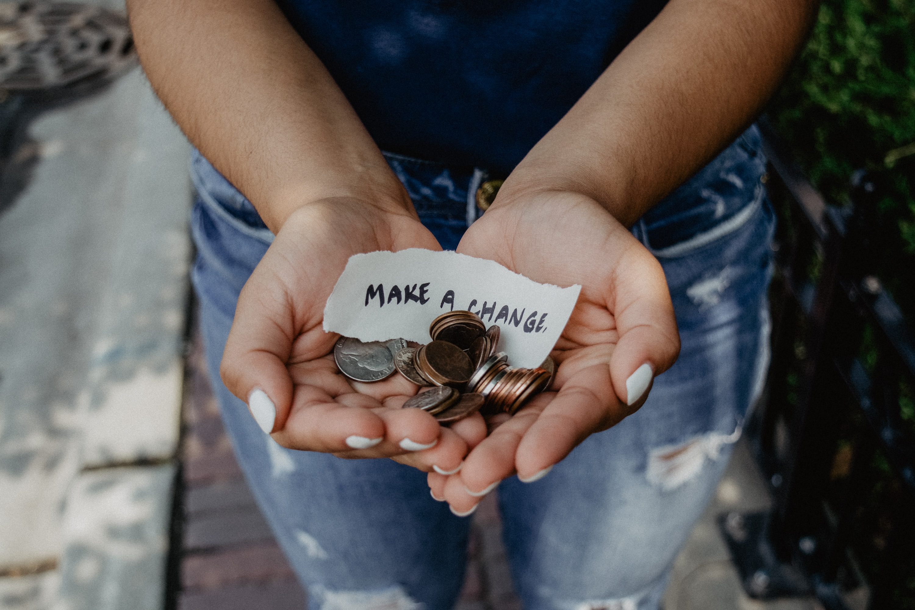 "close up of female hands holding coins and a note that says ""Make a Change"""