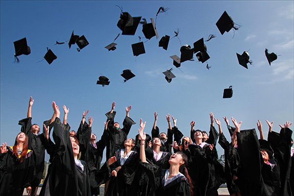 graduates throwing their mortarboards into the air