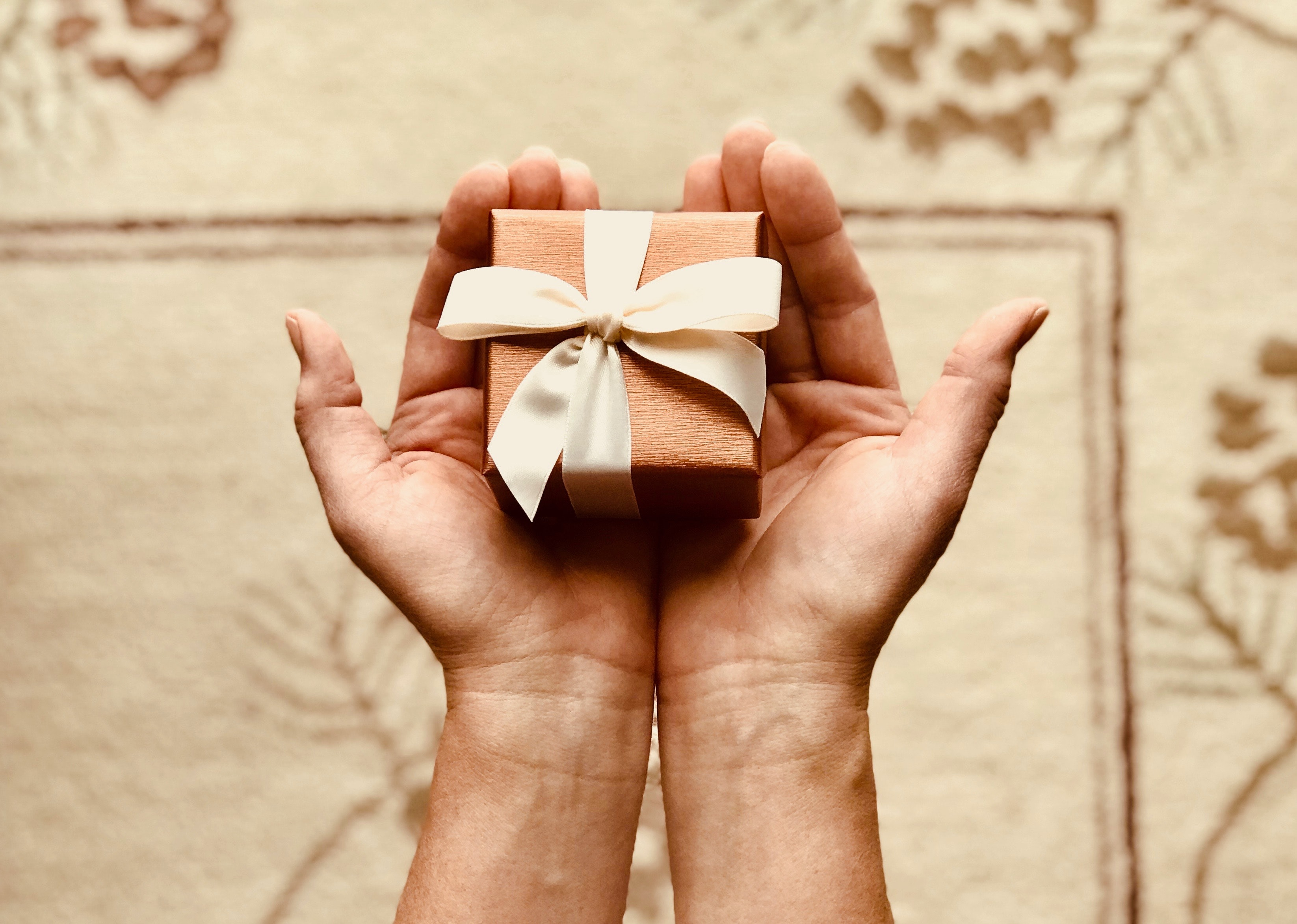 overhead shot of two hands holding a small gift wrapped with a bow