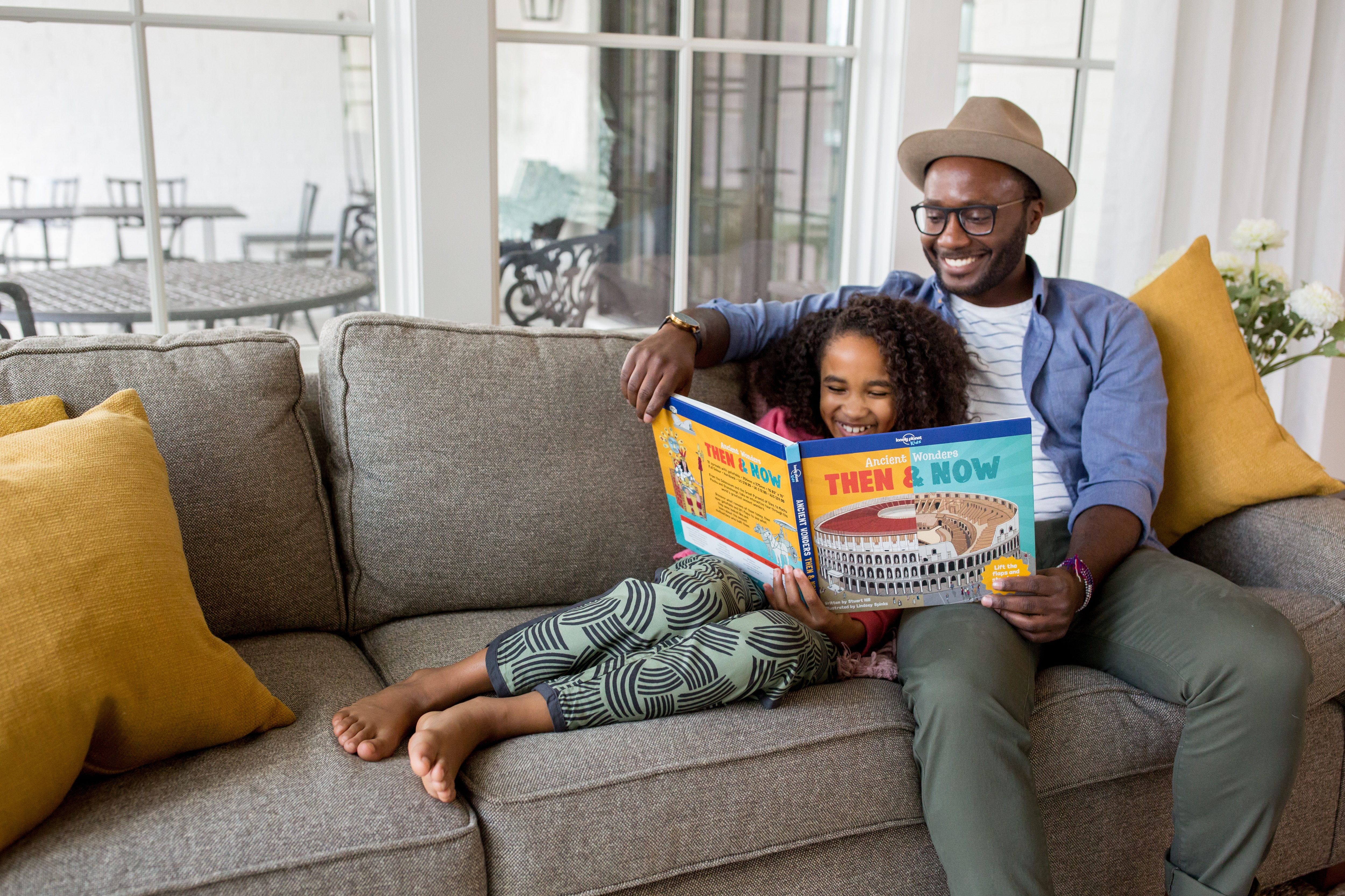 image of a father and daughter sitting on a couch and reading a book together