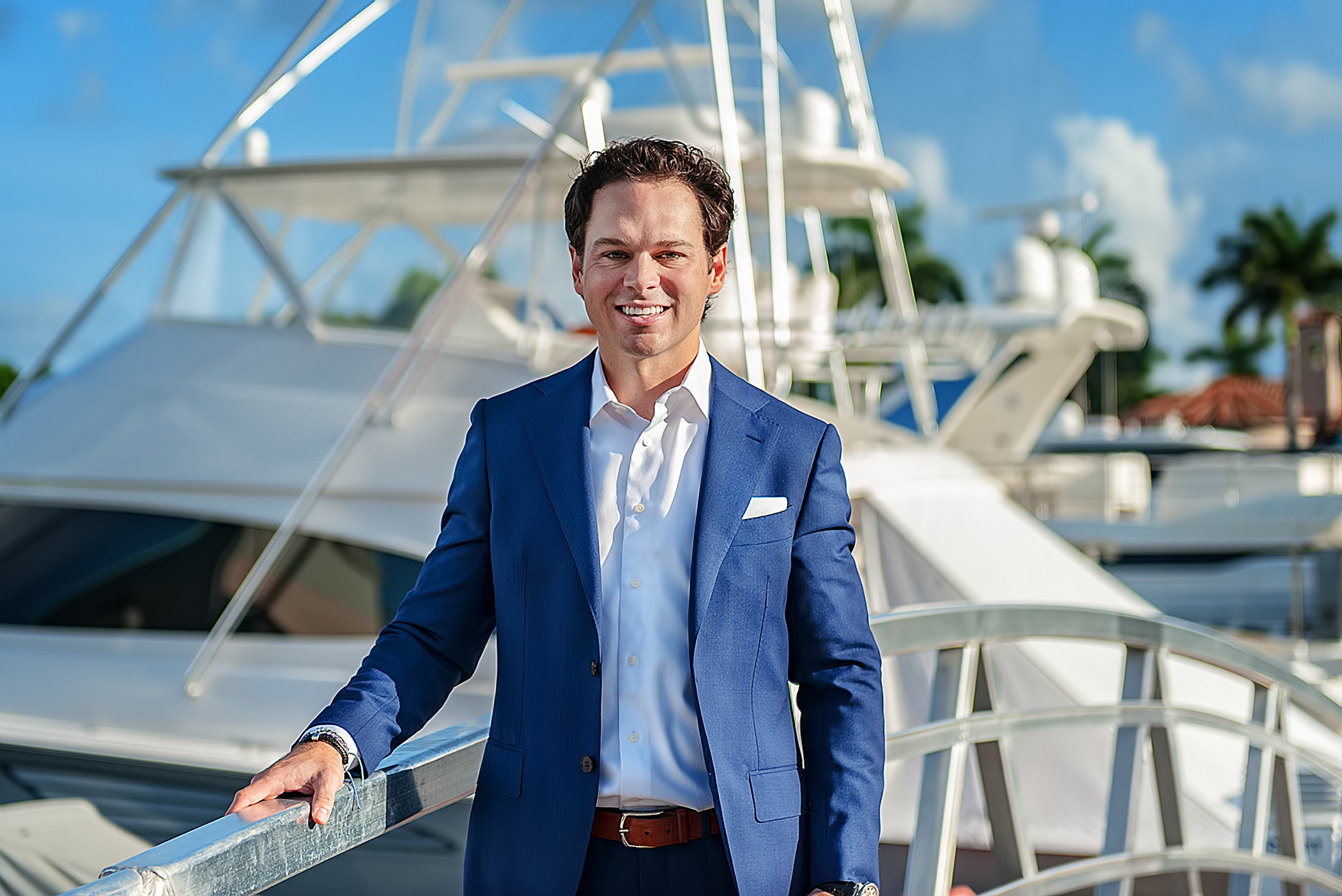 Mike Hennessy, CFA, CFP® standing in front of fishing boat wearing a blue suit and white shirt