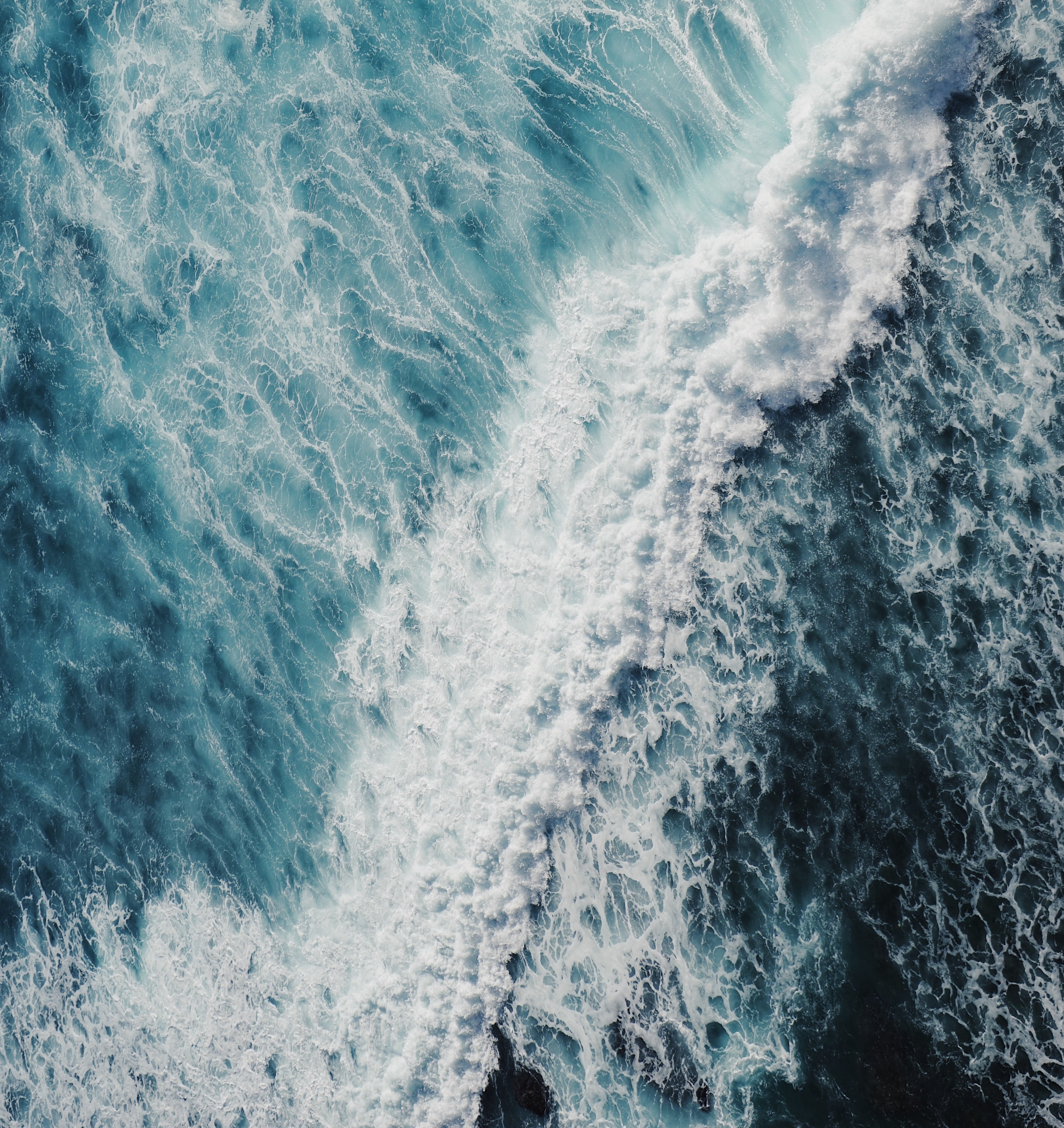 Aerial view of dark blue white-capped waves churning in the ocean