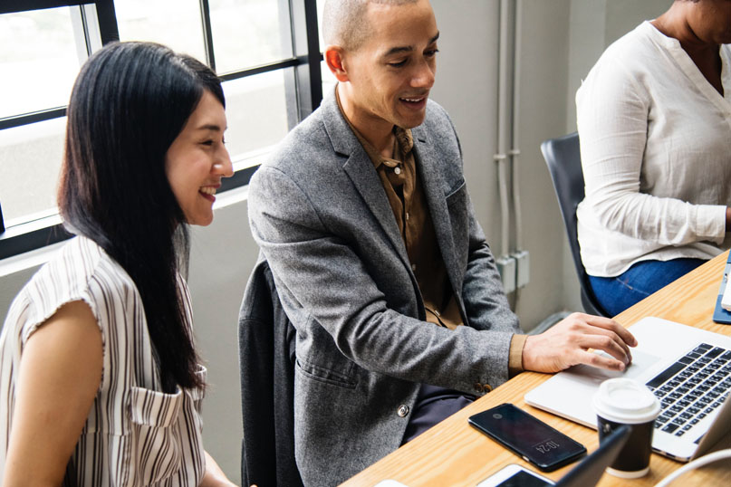 Man and Woman Smiling at Computer