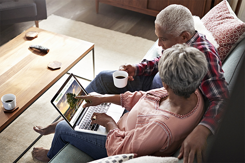 KWB Wealth | Redlands, CA: mature couple on couch viewing laptop