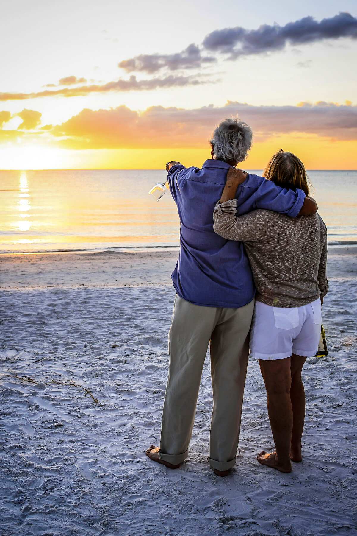 Older couple looking out at beach sunset
