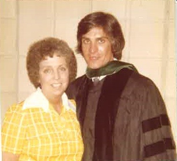 Dr. Joseph Hollen with his mother wearing his gown for his medical school graduation. Dr. Joseph's mother is wearing a yellow and white plad shirt. She is standing to Dr. Joseph's right with her arm around his back.