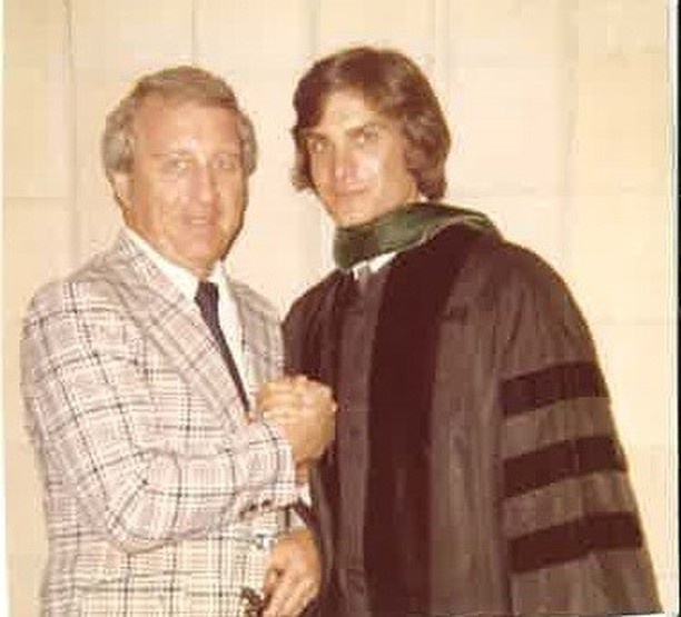 Dr. Joseph Hollen with his father wearing his gown for his medical school graduation. Dr. Joseph's father is wearing a white plad suit jacket and tie. Hollen senior is standing very close to Dr. Joseph's left.
