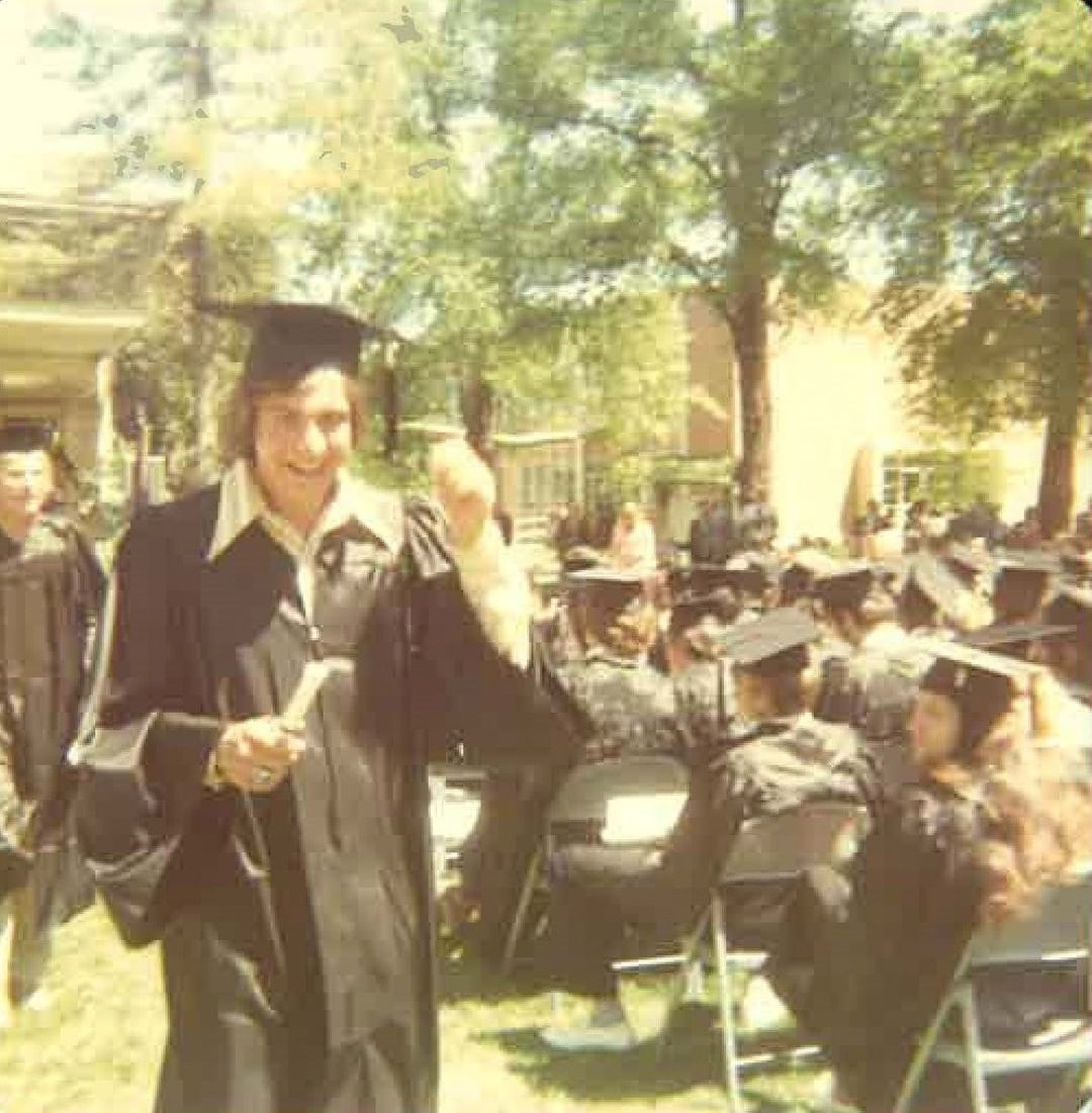 Young Dr. Joseph Hollen at his undergraduate graduation. He has a black cap and gown on and is walking back to his seat during his graduation with a big smile on his face while holding his tassel in his left hand. The photo is faded.