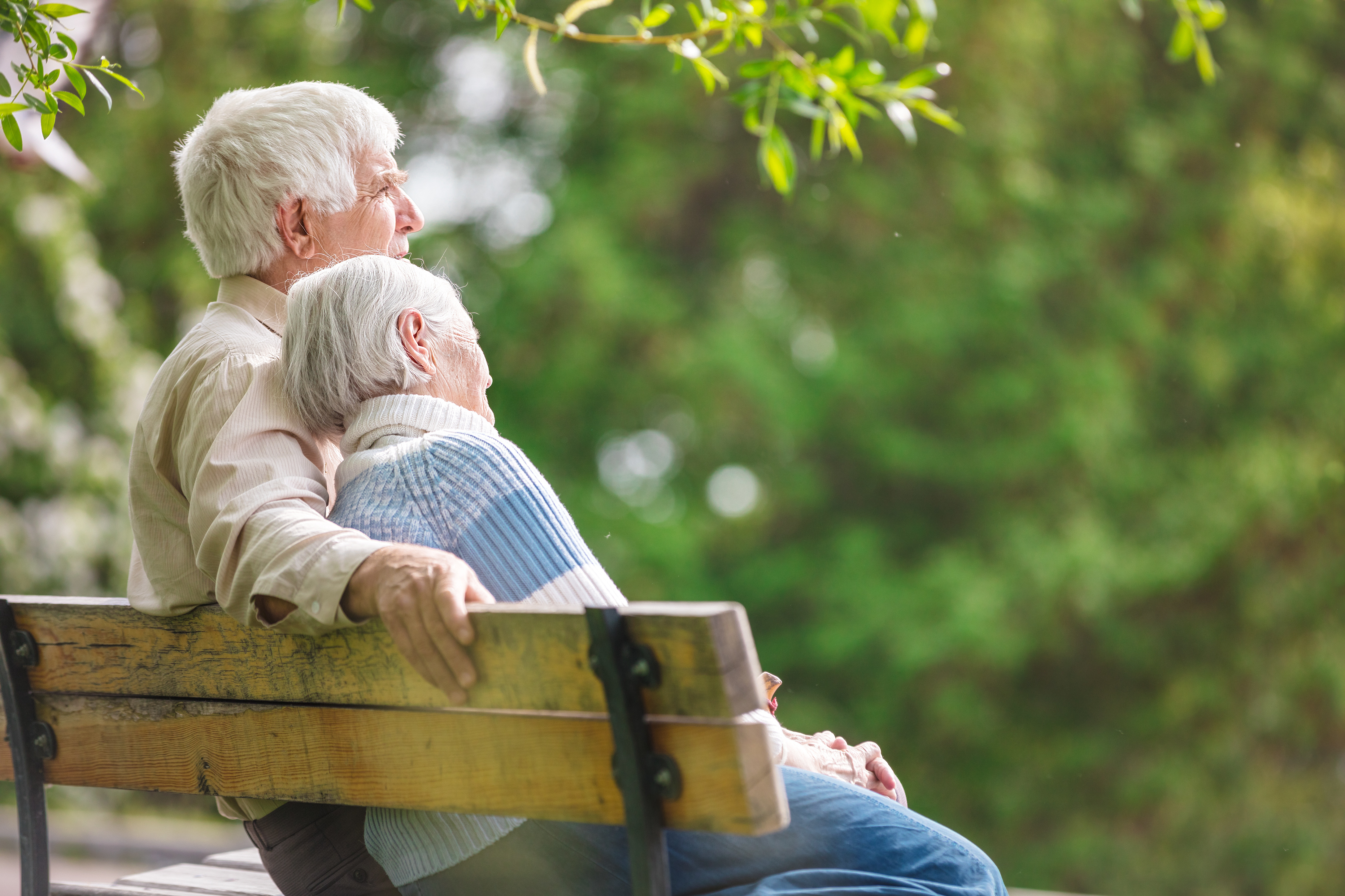Elderly couple sitting on a bench enjoying retirement