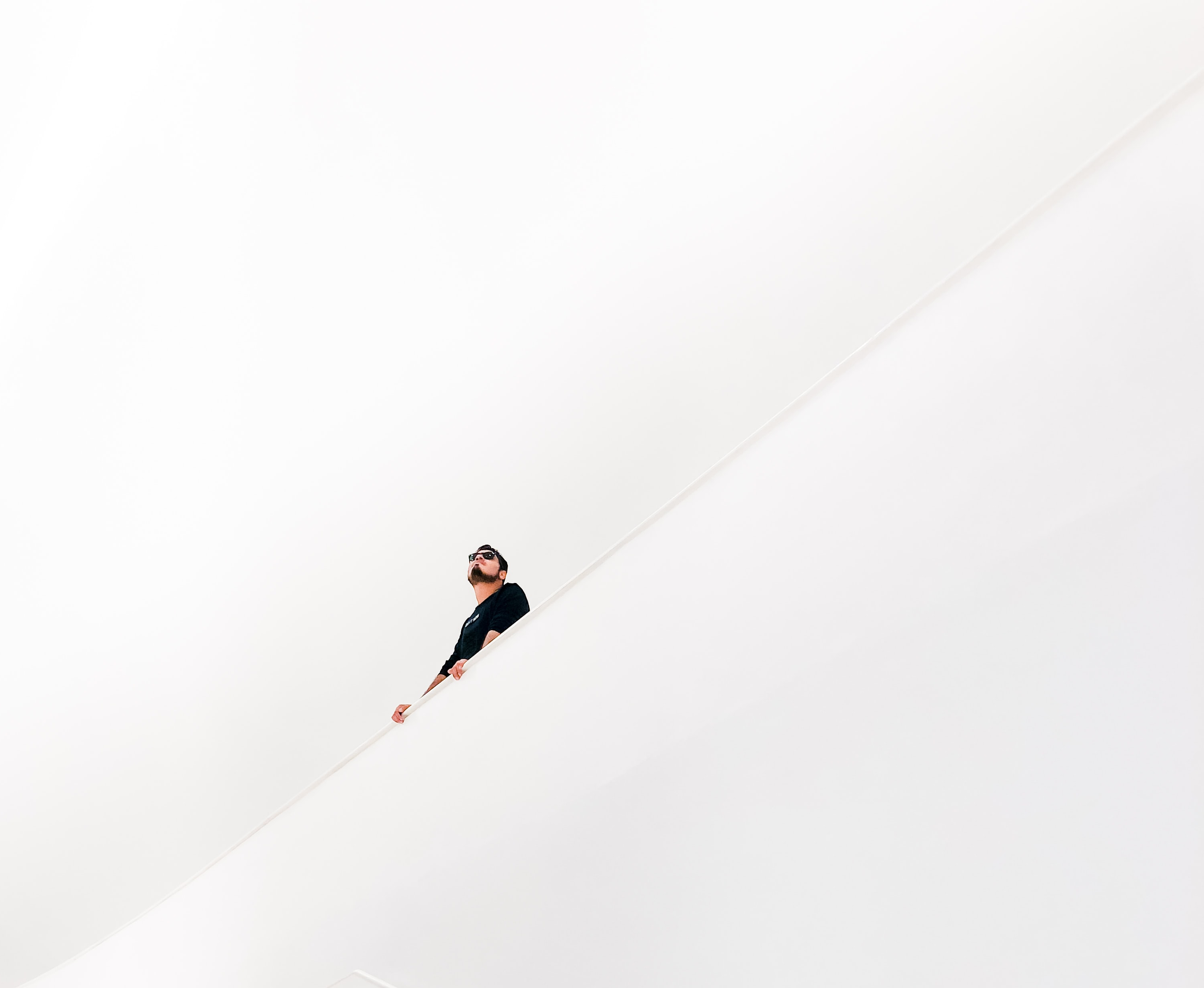 Man looking up in white stairwell