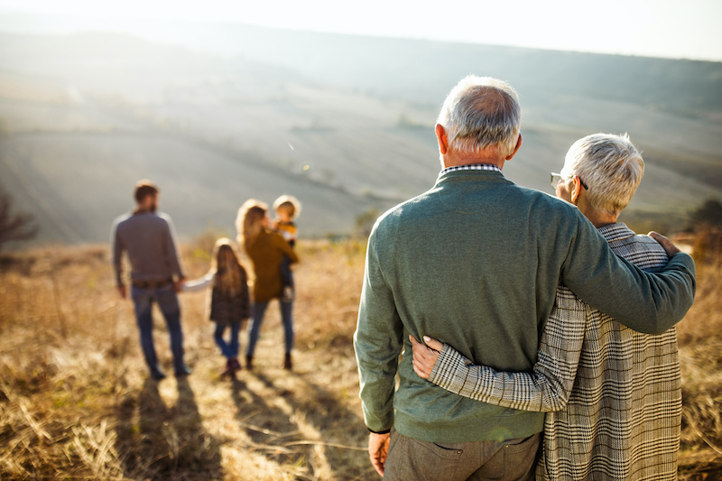 A retired couple in the outdoors, looking down a hill at their children and grandchildren Boca Raton, FL Freedom Family