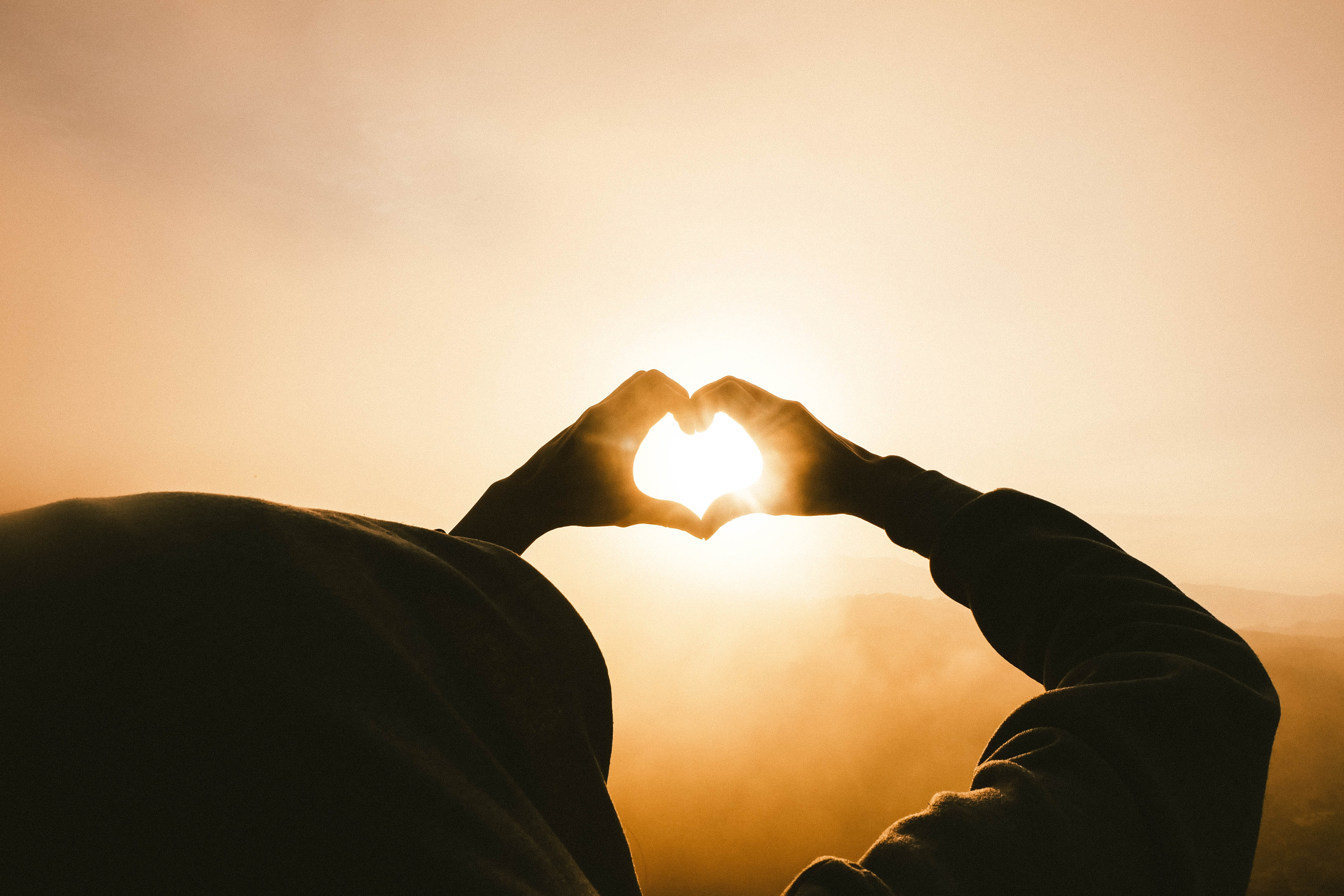 Silhouette hands making a heart shape pointed towards sun