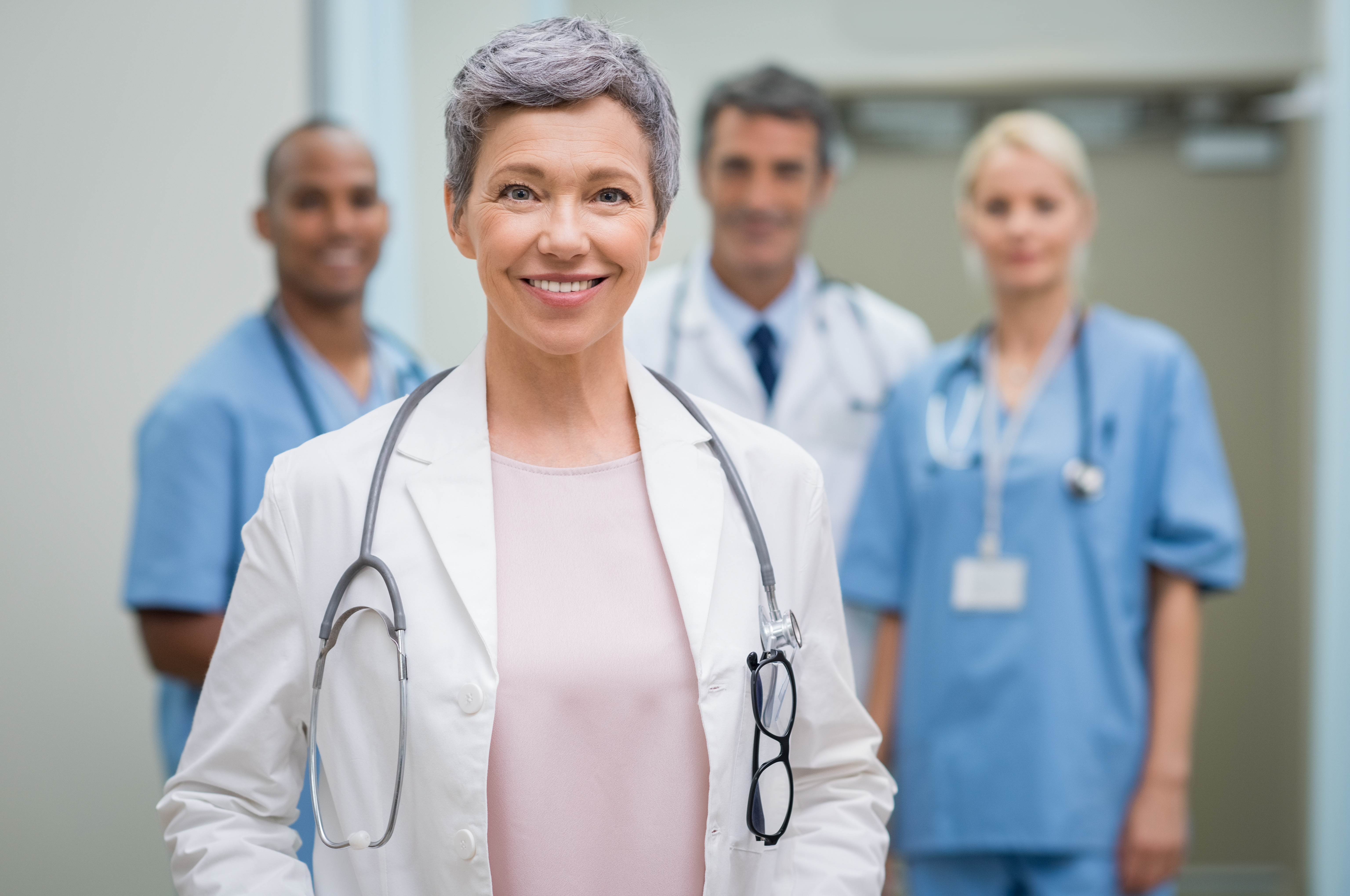Photo of a female nurse with gray hair smiling, other nurses are out of focus in the background