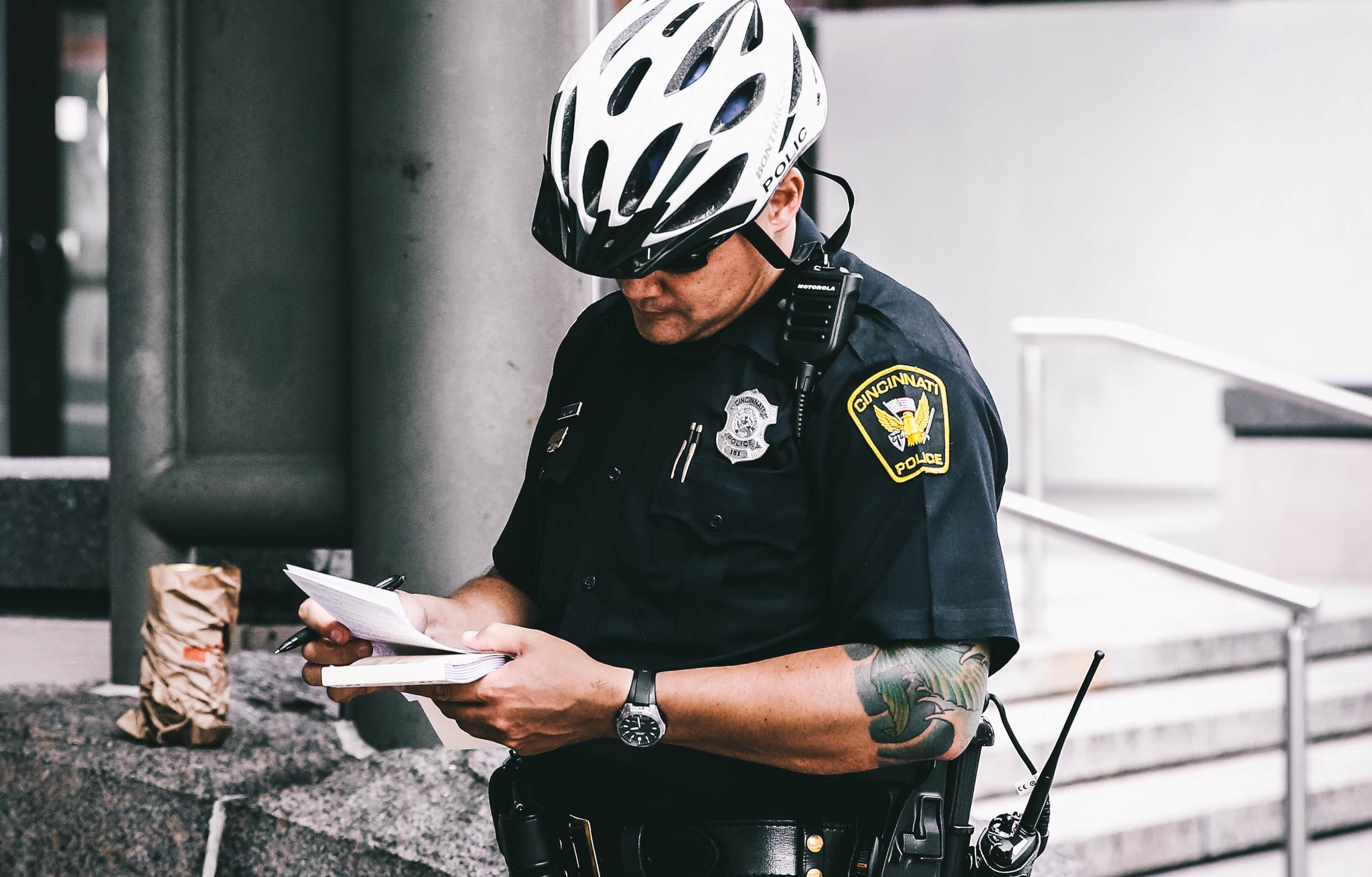 Police officer holding notebook and wearing bicycling helmet.