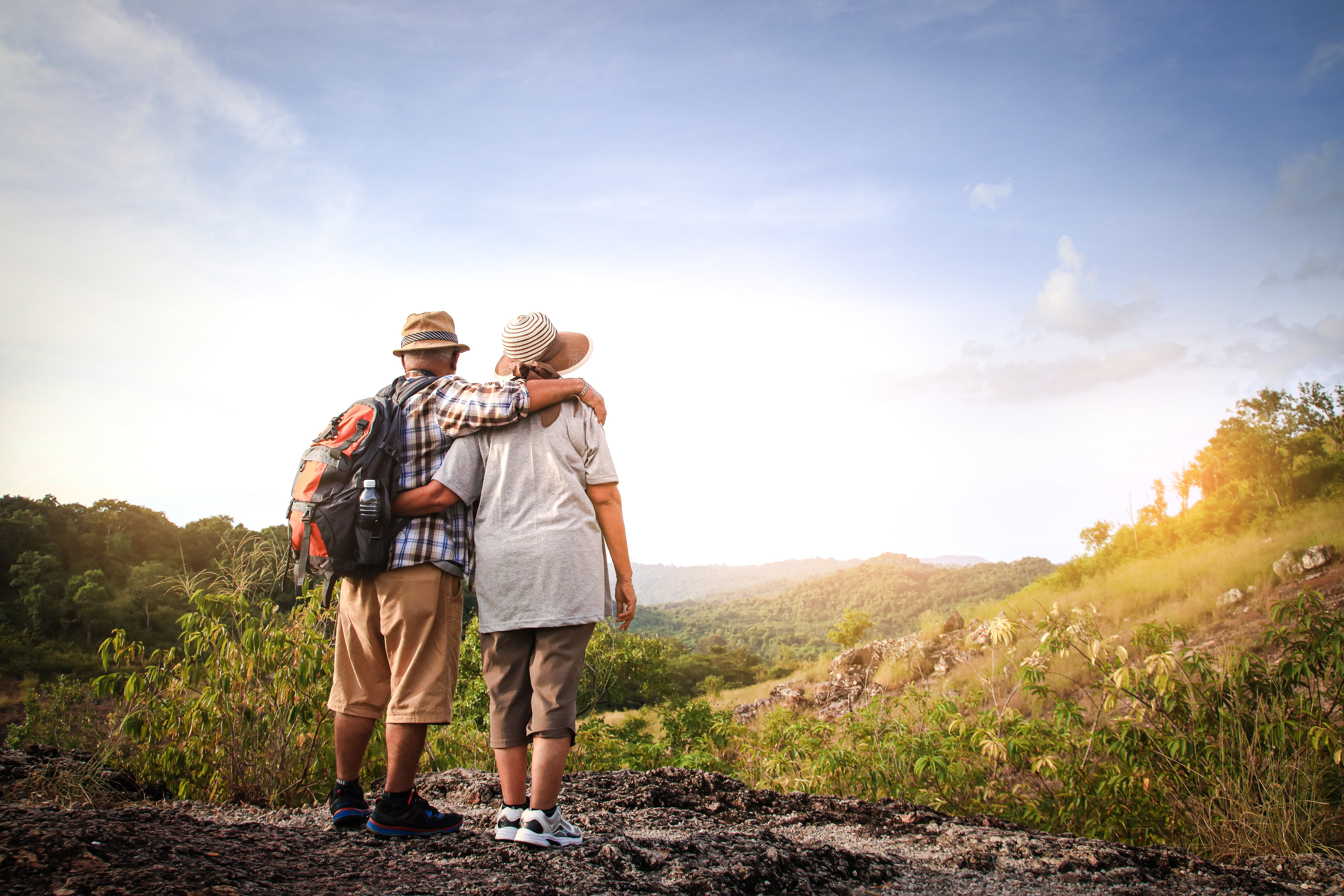 Older couple hiking up a mountain.