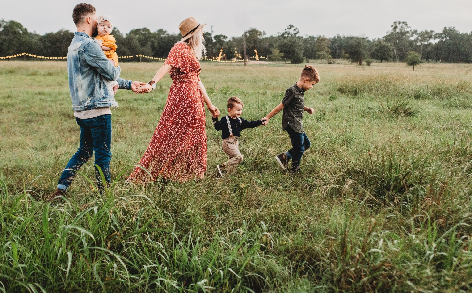 Photo of young parents walking with their 3 children through a field at daytime