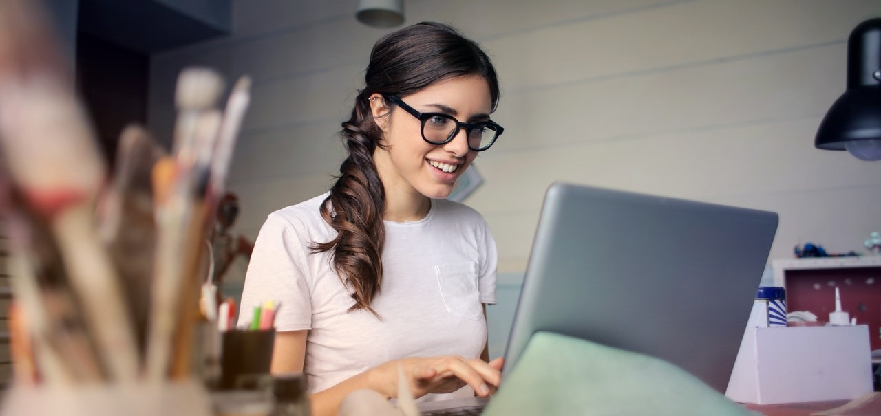 Young woman wearing glasses smiling while looking at a computer screen