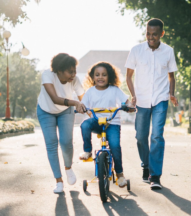Young parents smile as they help their young child learn to ride a bike
