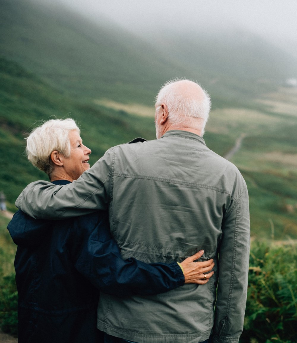 mature couple with white hair looking at each other while standing on a trail ontop a hill.