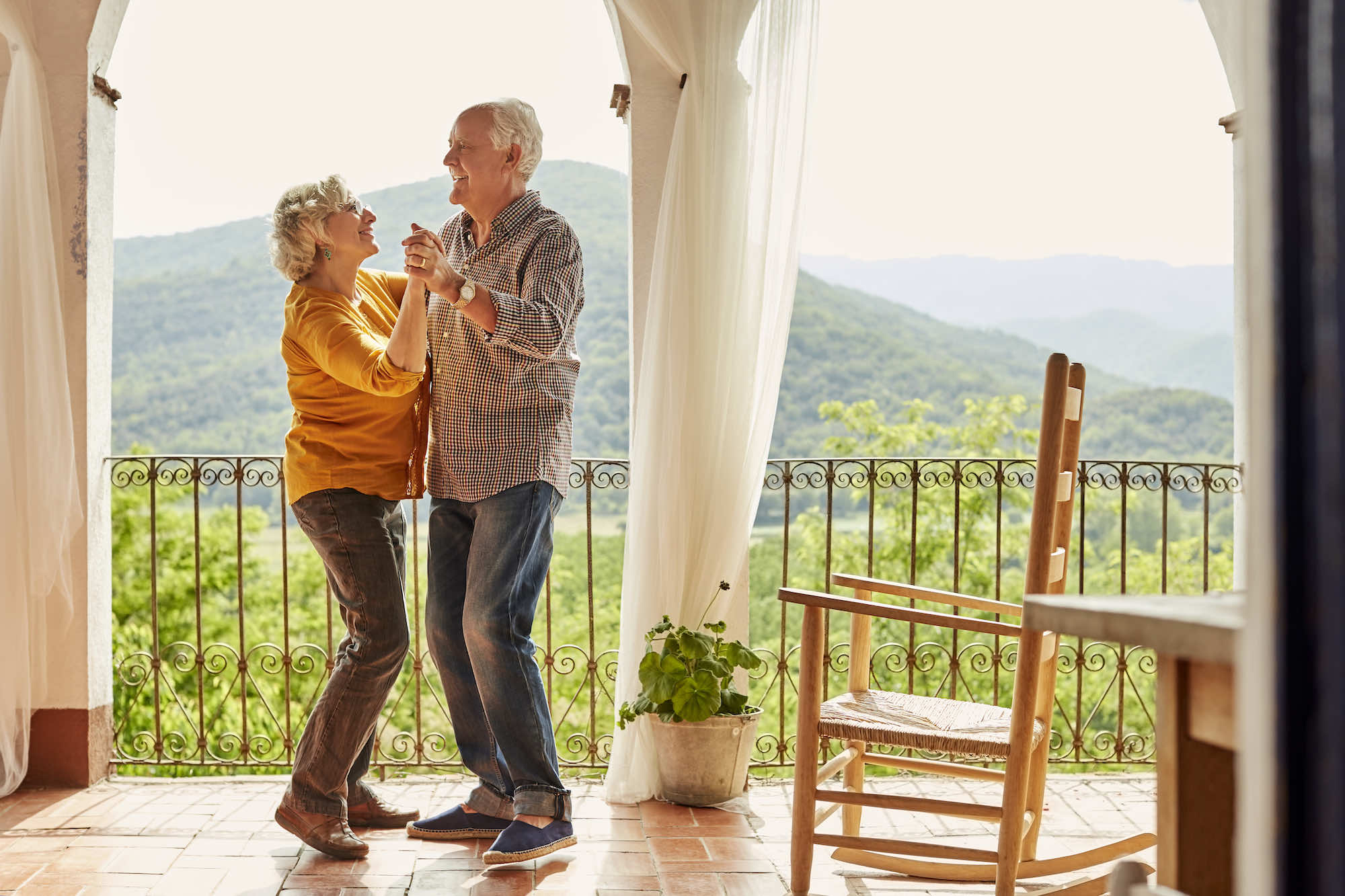 Retired couple dancing on house balcony