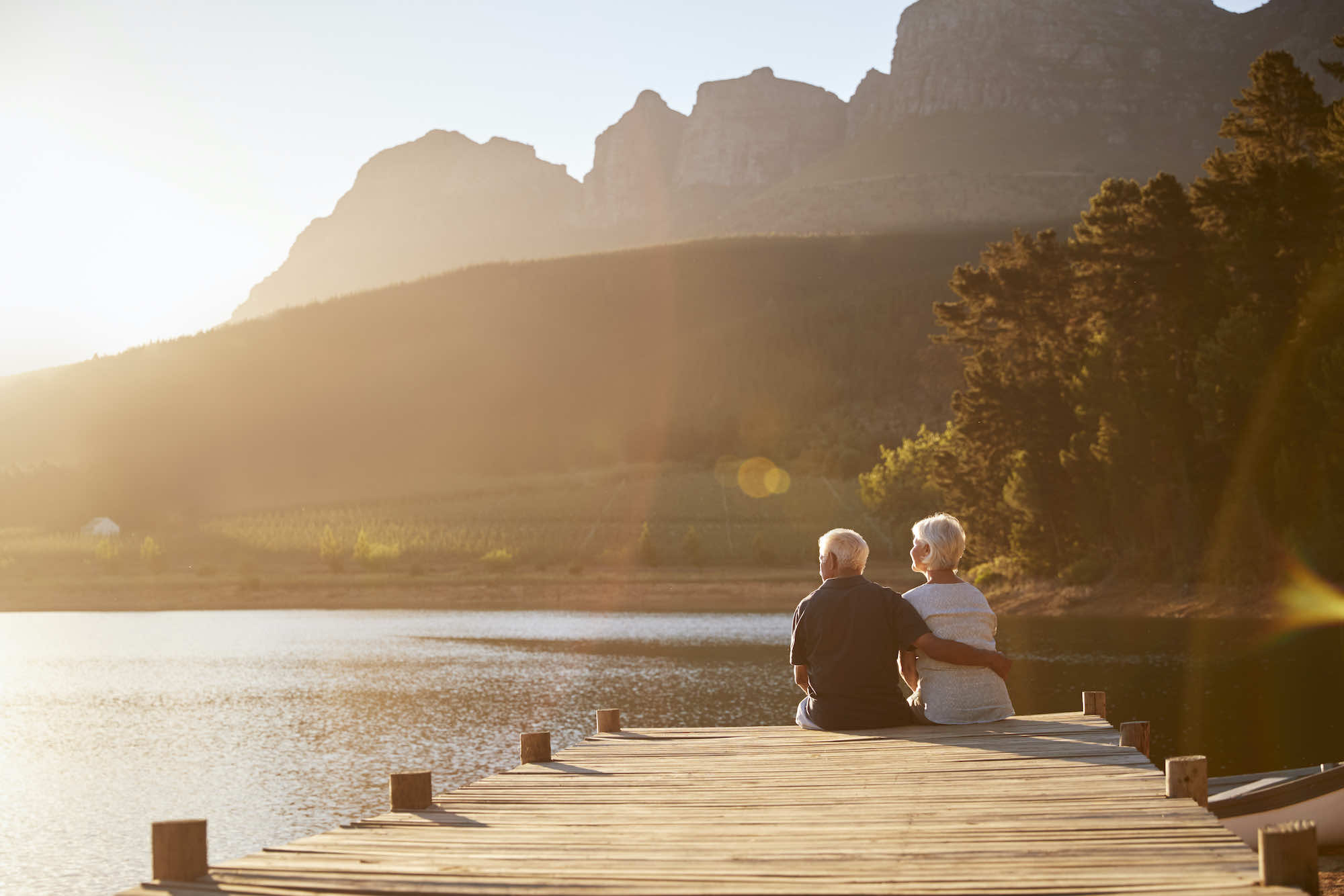 Older couple sitting at the end of a dock watching sunset