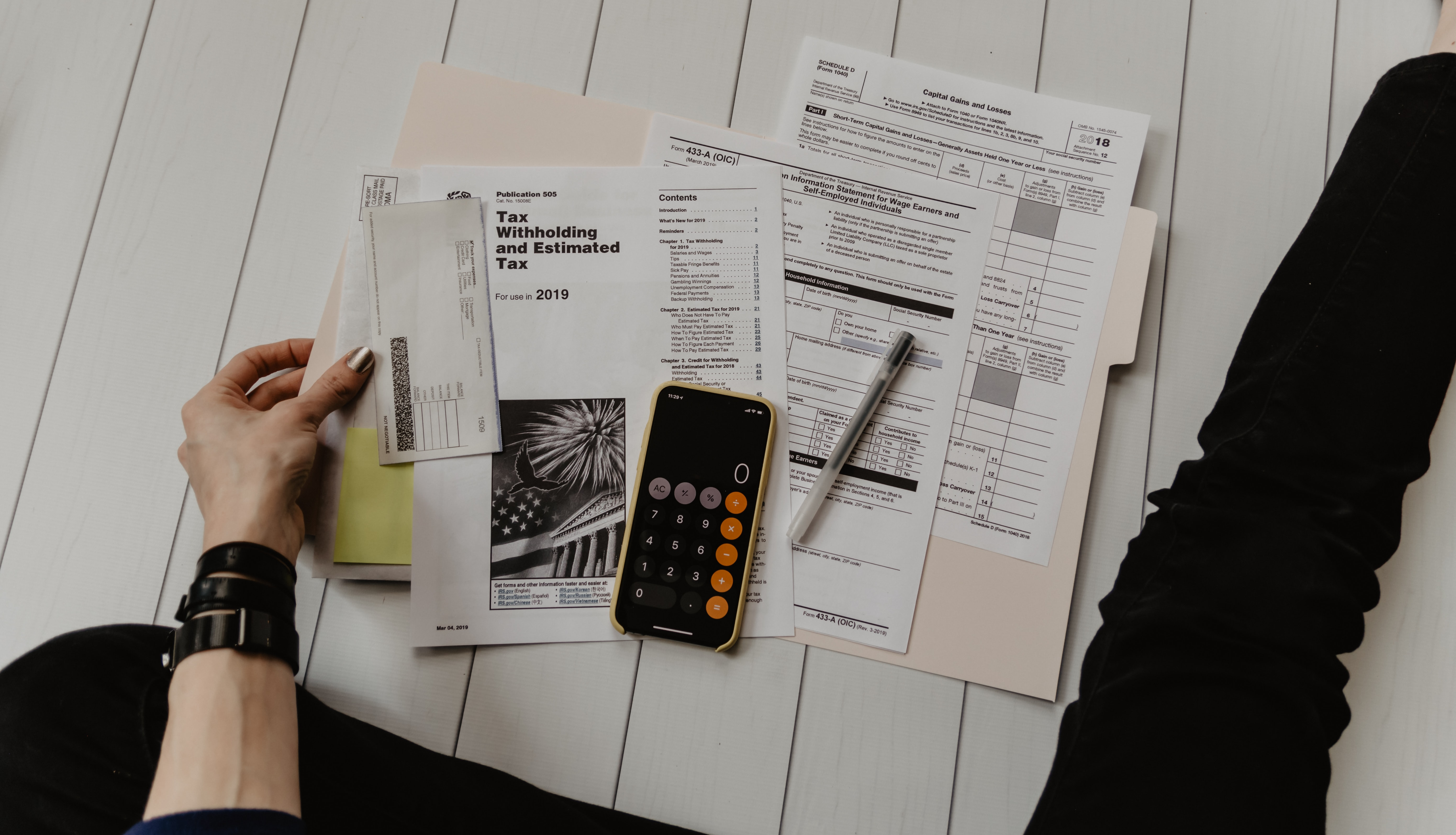 person with tax documents and calculator