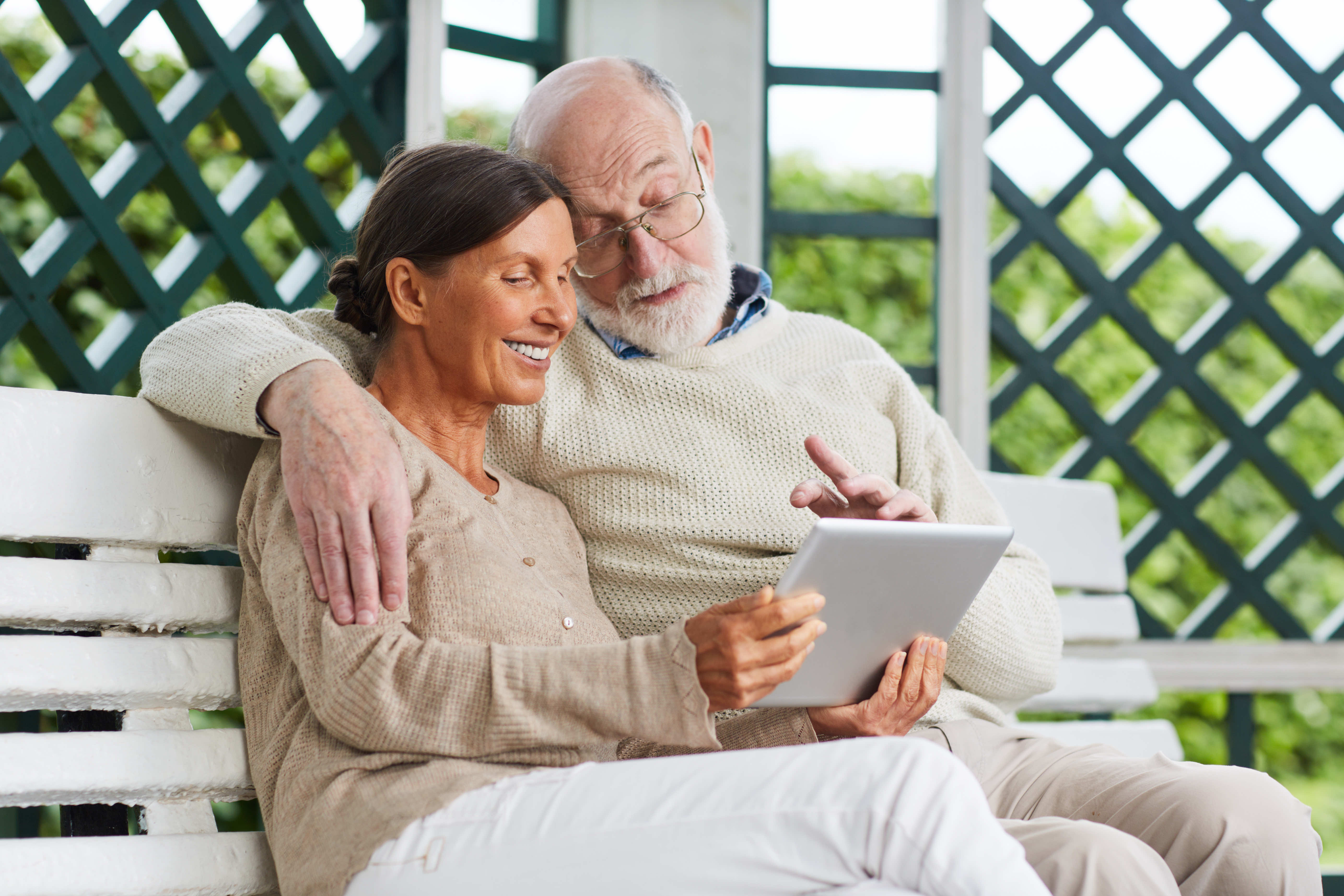 Retired couple reading an article on a tablet