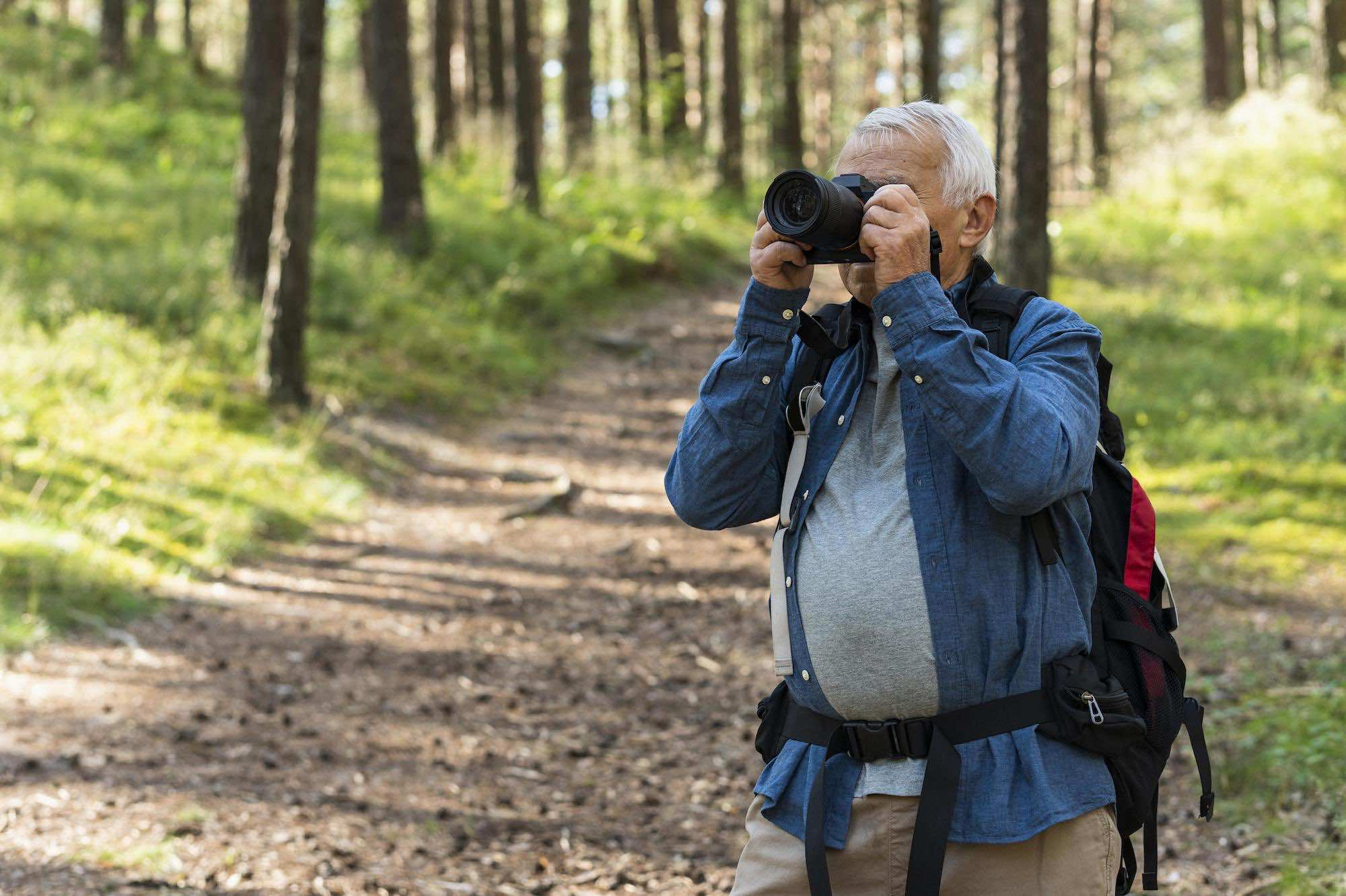 Older man exploring nature with camera