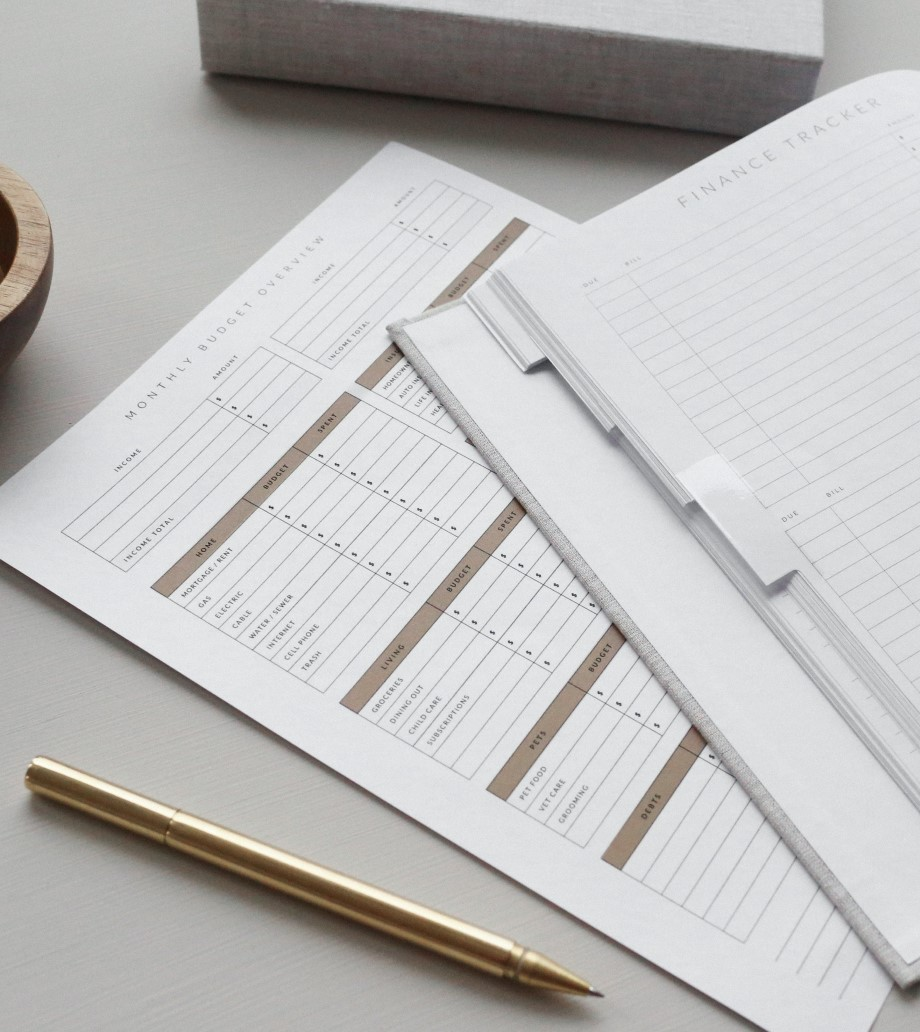 Closeup photo of a stack of papers on a desk, including budget reports and finance trackers.