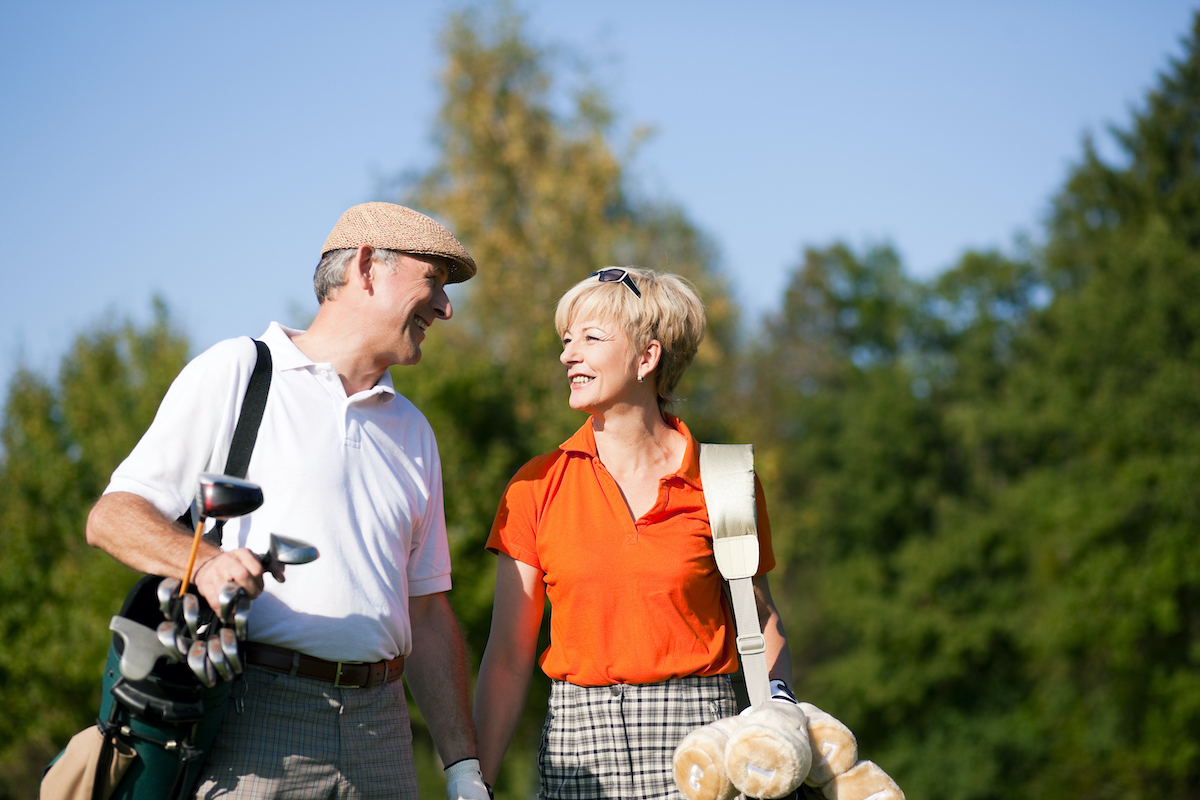 Retired couple walking on a golf course