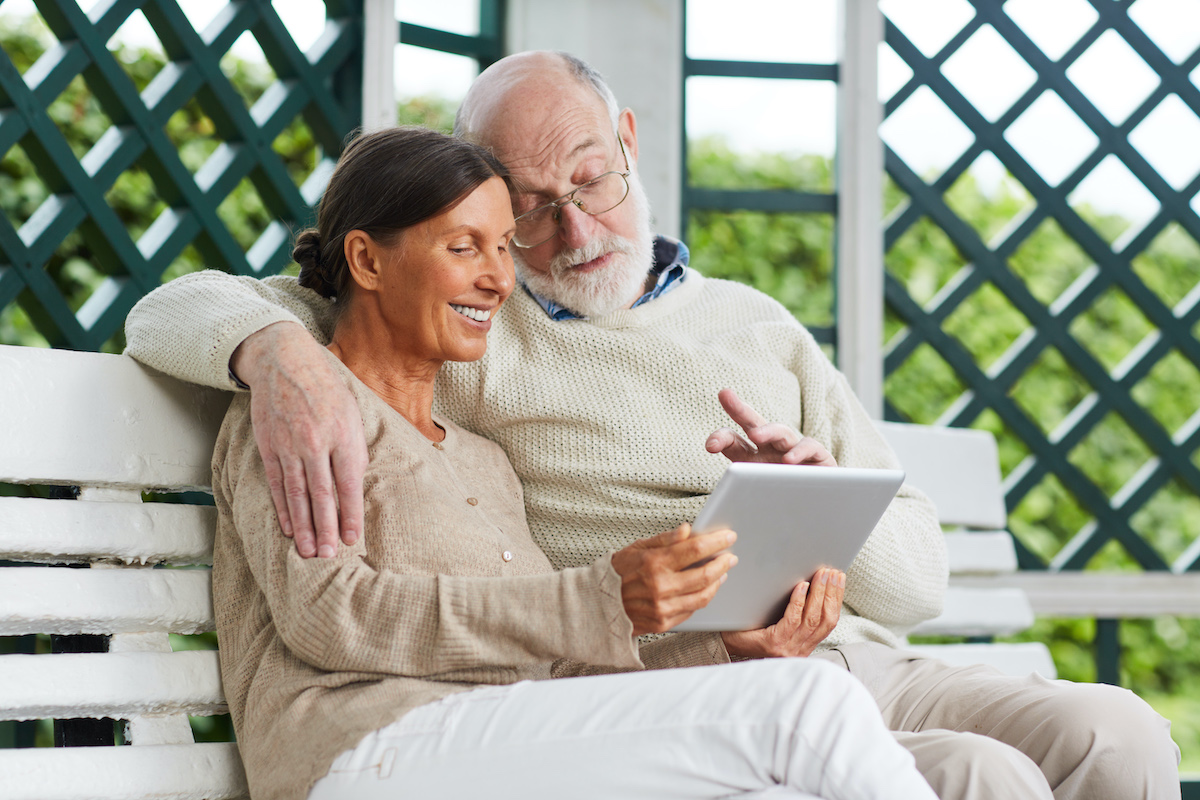 Older couple looking at a tablet together on a bench