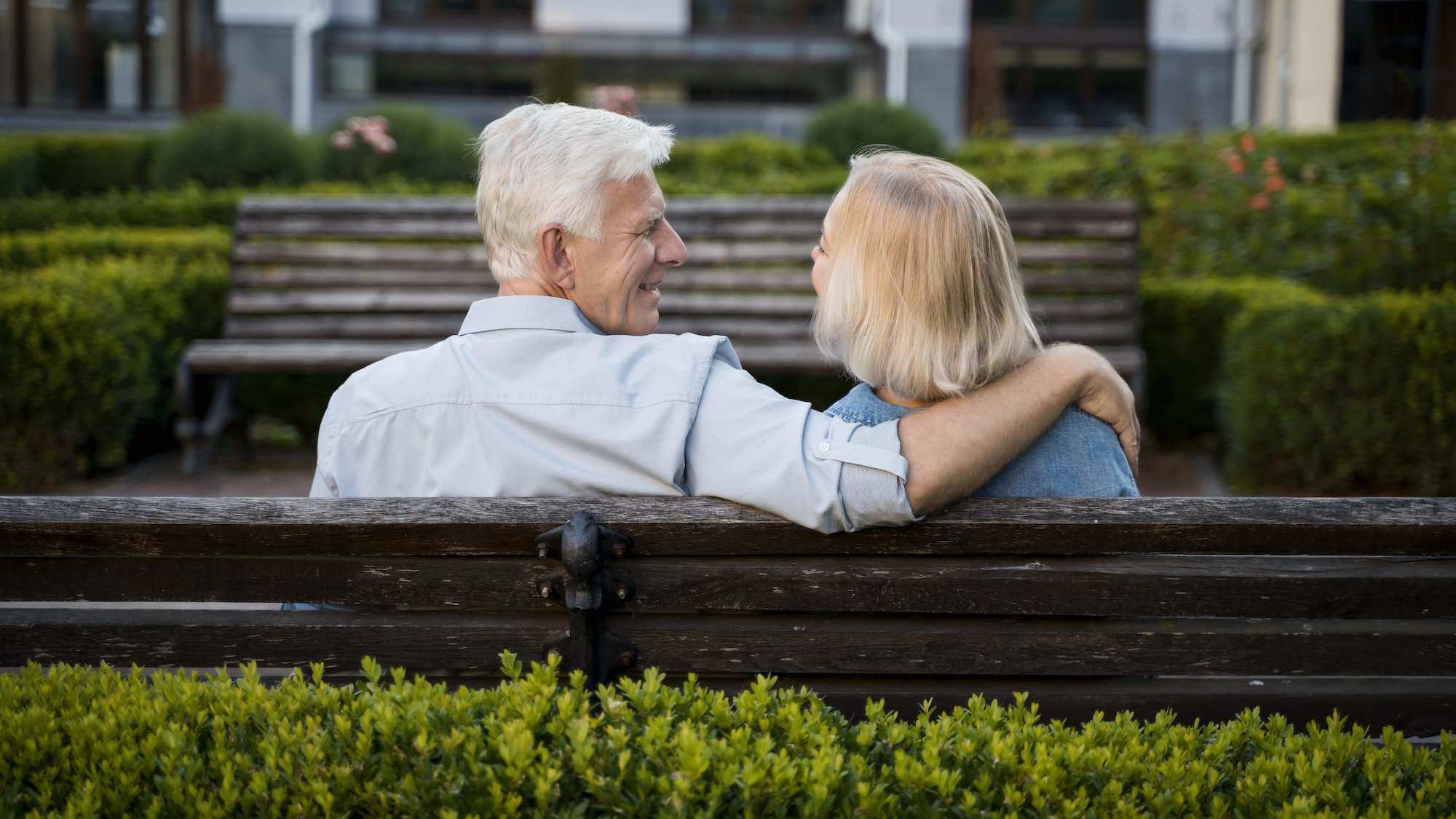 retired couple sitting on park bench