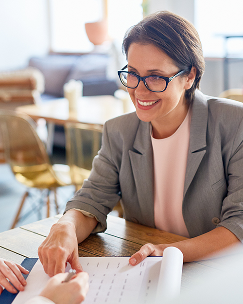 A middle aged woman in business attire smiles as she looks over paperwork.