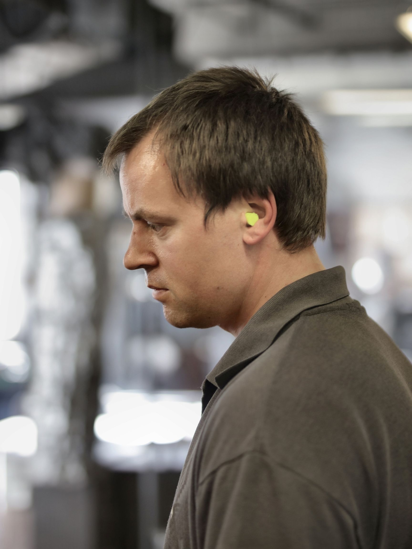 Side profile of a middle aged man wearing earplugs inside a factory.
