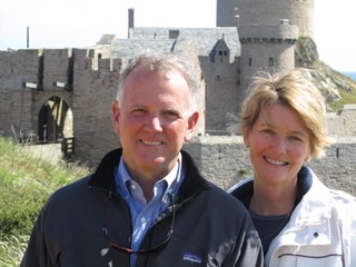 Rob and his wife smiling at the camera infront of a castle.