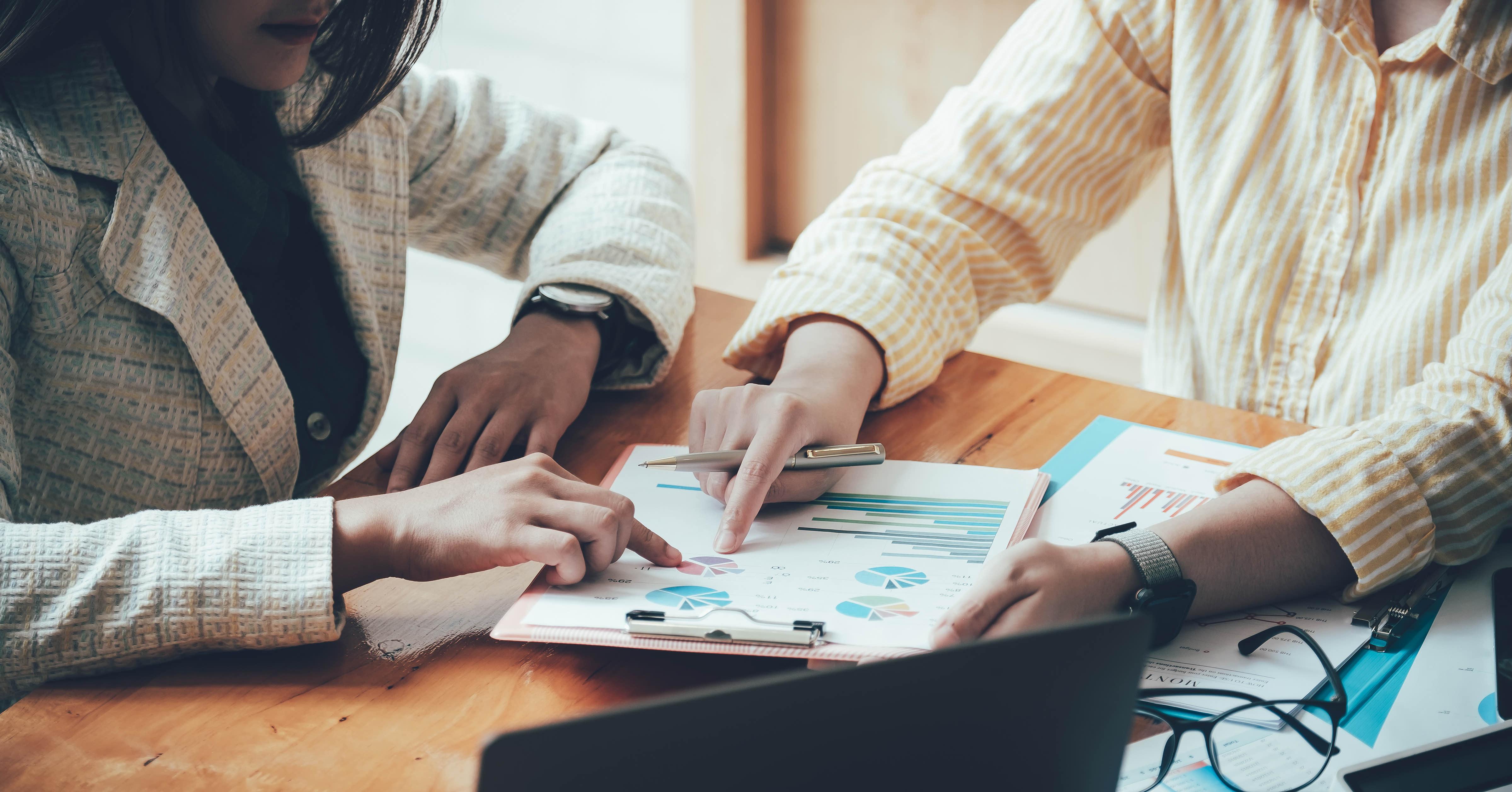 Man and women looking at financial charts.