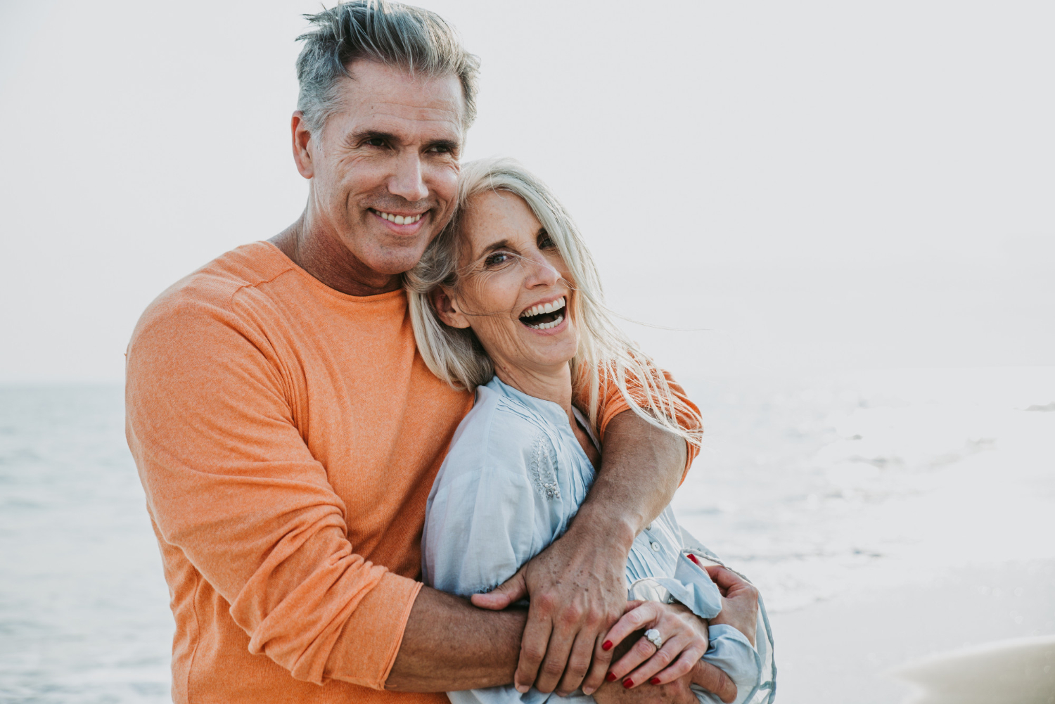 Elderly couple hugging and smiling on a beach.