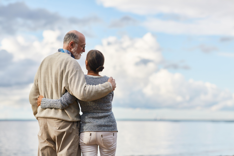 Couple standing in front of the ocean hugging.