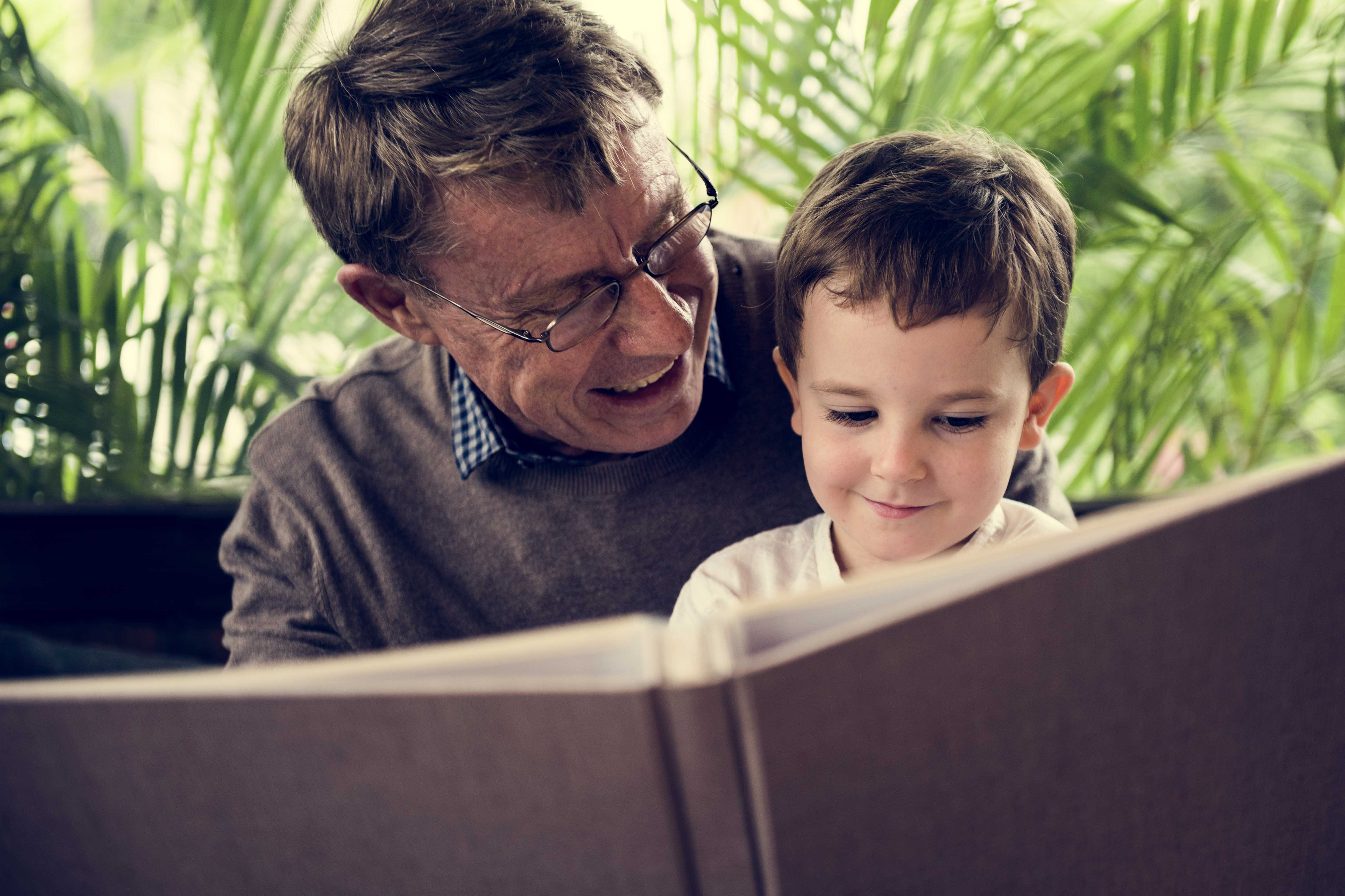 Grandfather reading a book with grandson