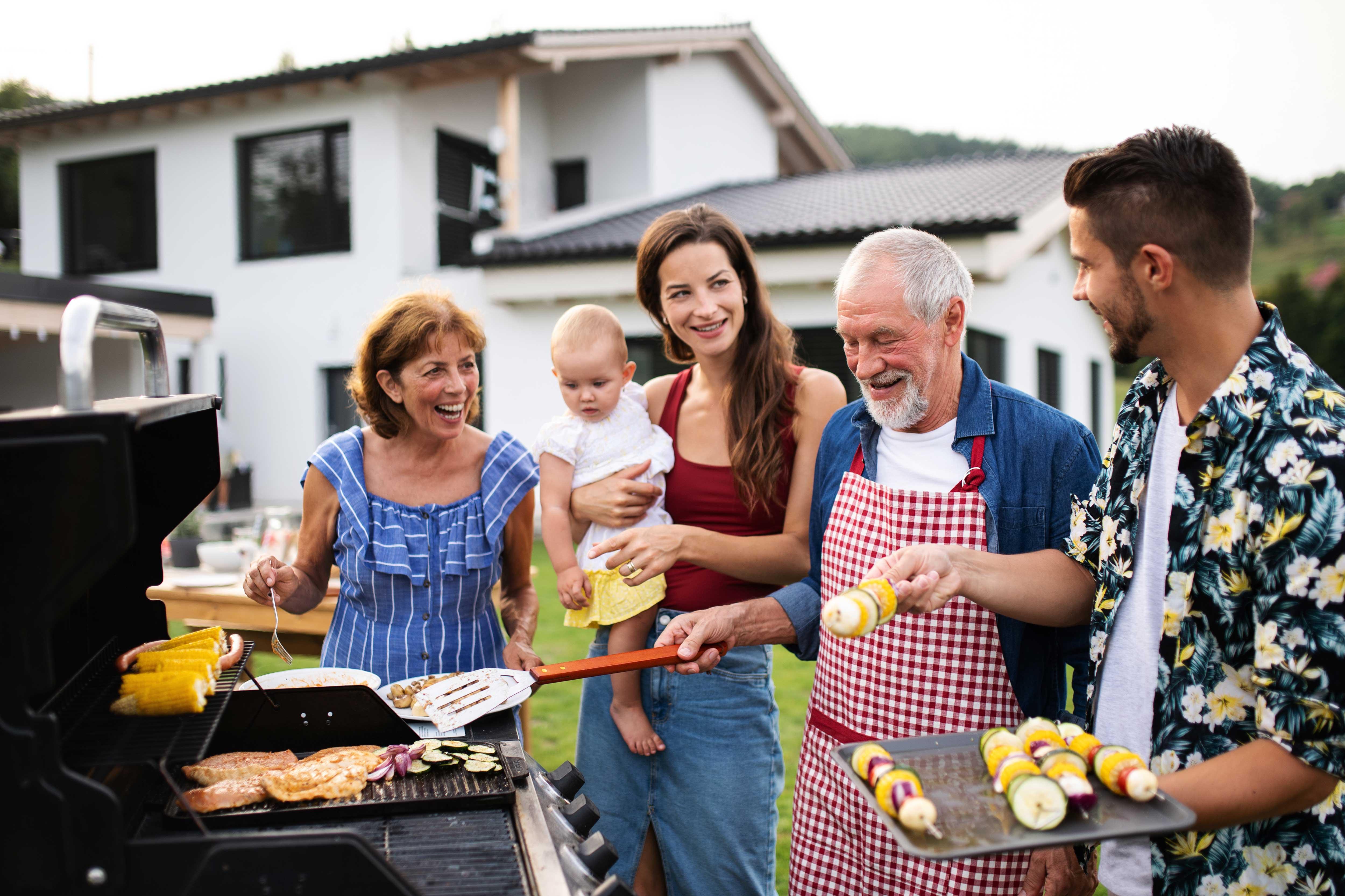 Multigenerational family enjoying BBQ in a backyard